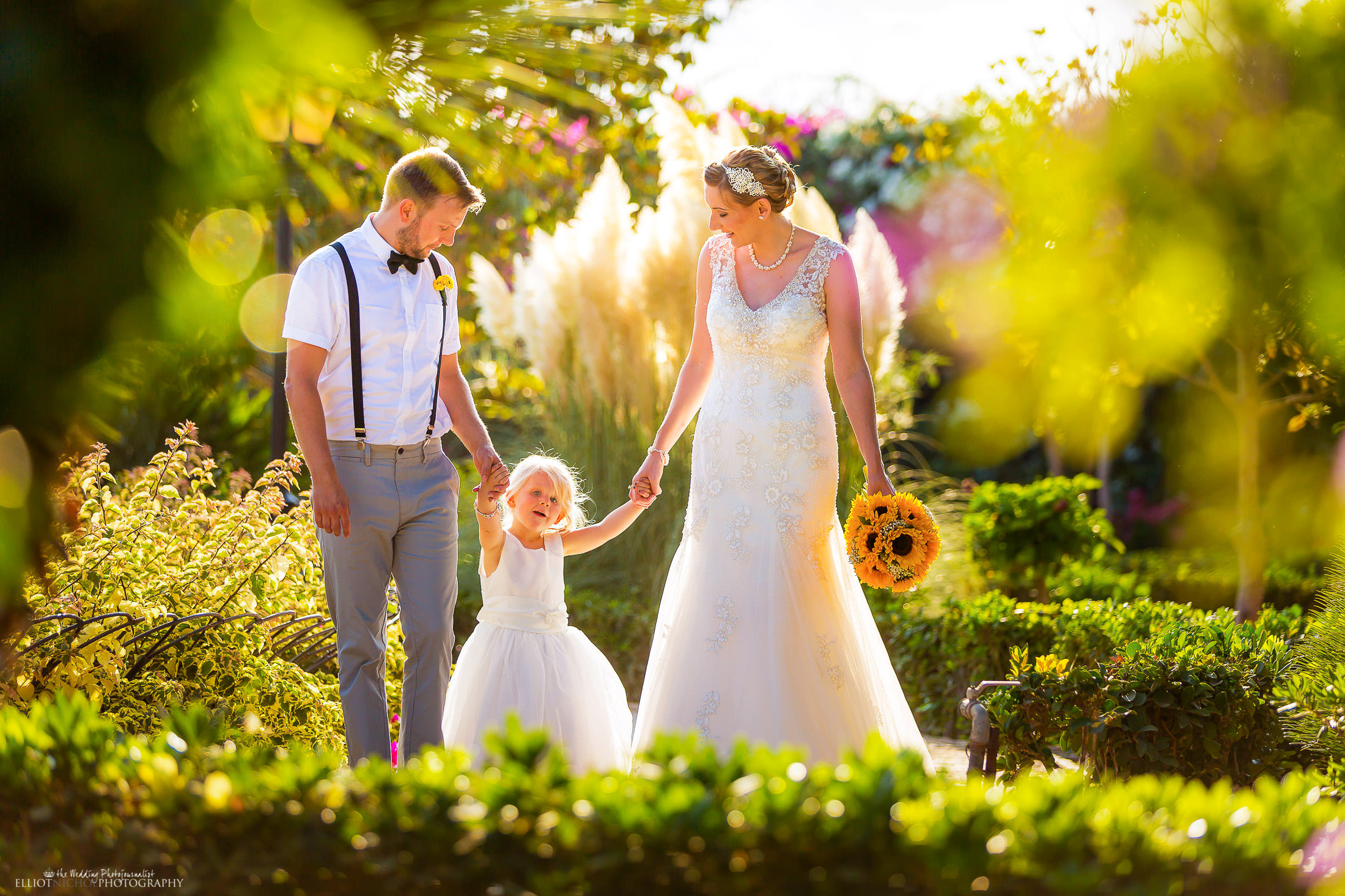 Newlywed couple take some time with their daughter in the gardens of their wedding venue. Photo by Newcastle based wedding photojournalist Elliot Nichol photographing wedding both in the UK and abroad.