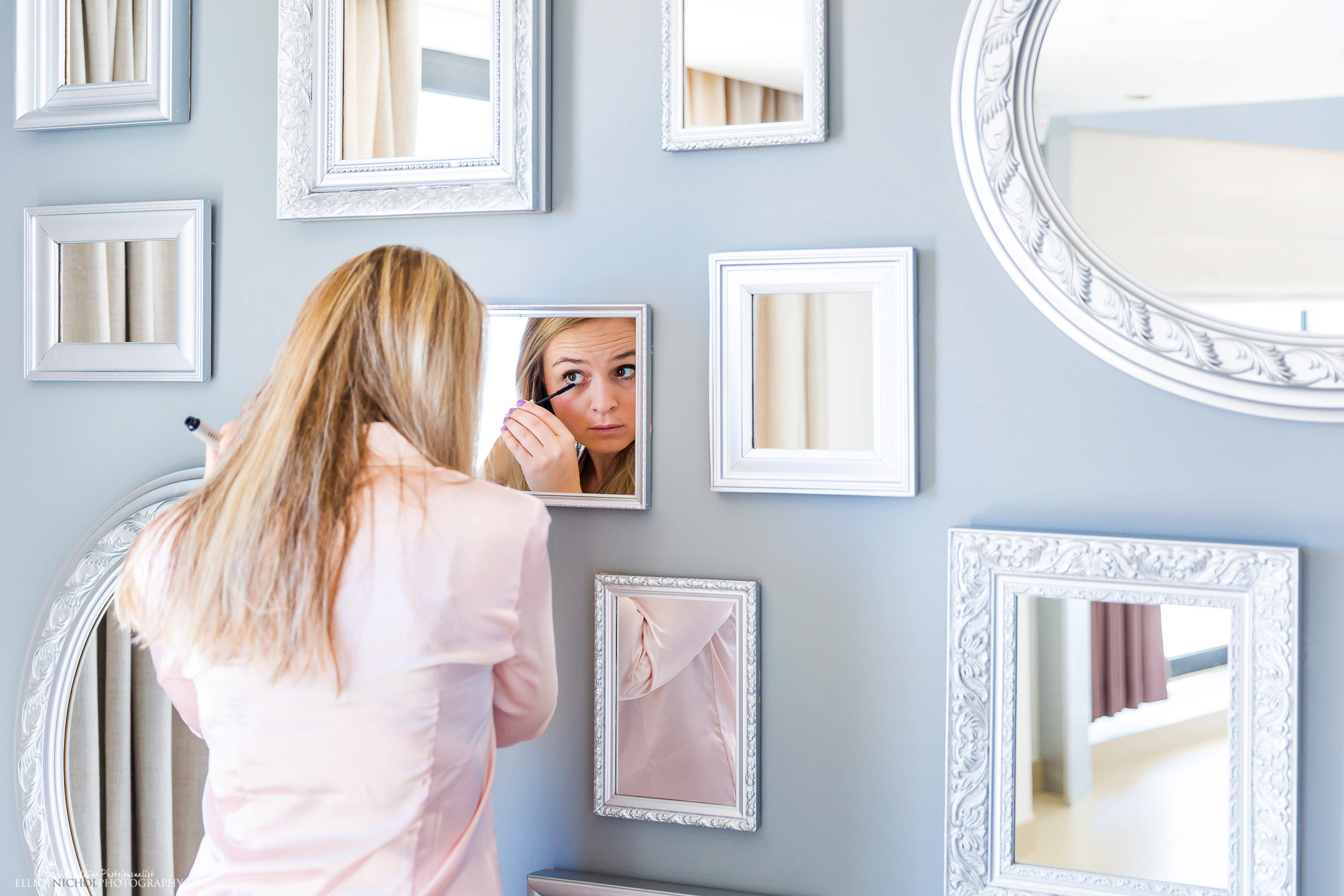 Bridesmaid getting ready in one of the many mirrors on the wall. Photo by Elliot Nichol Photography.
