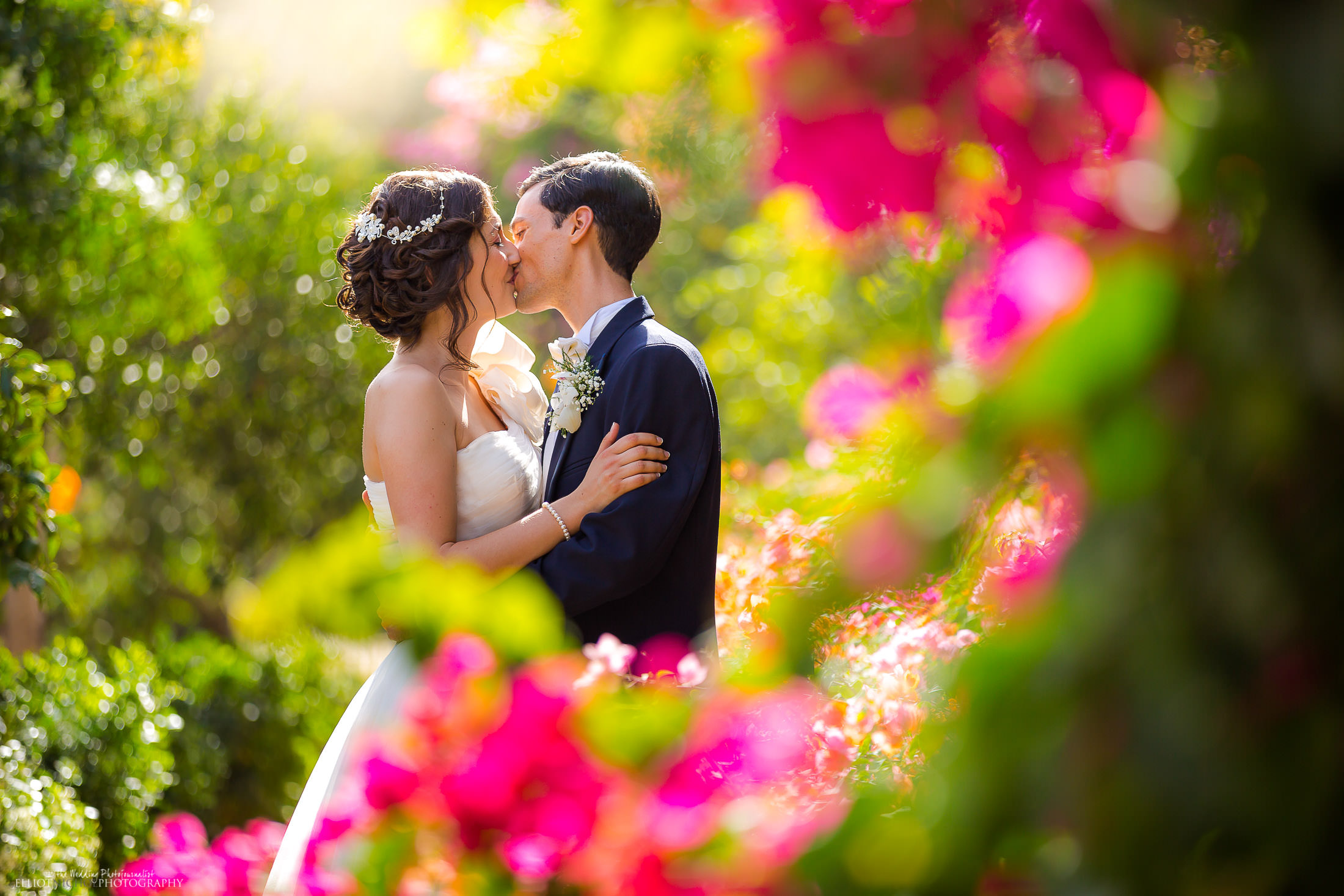 Bride & Groom kiss in the colourful gardens of their wedding reception venue. Photo by Northeast wedding photographer, Elliot Nichol.