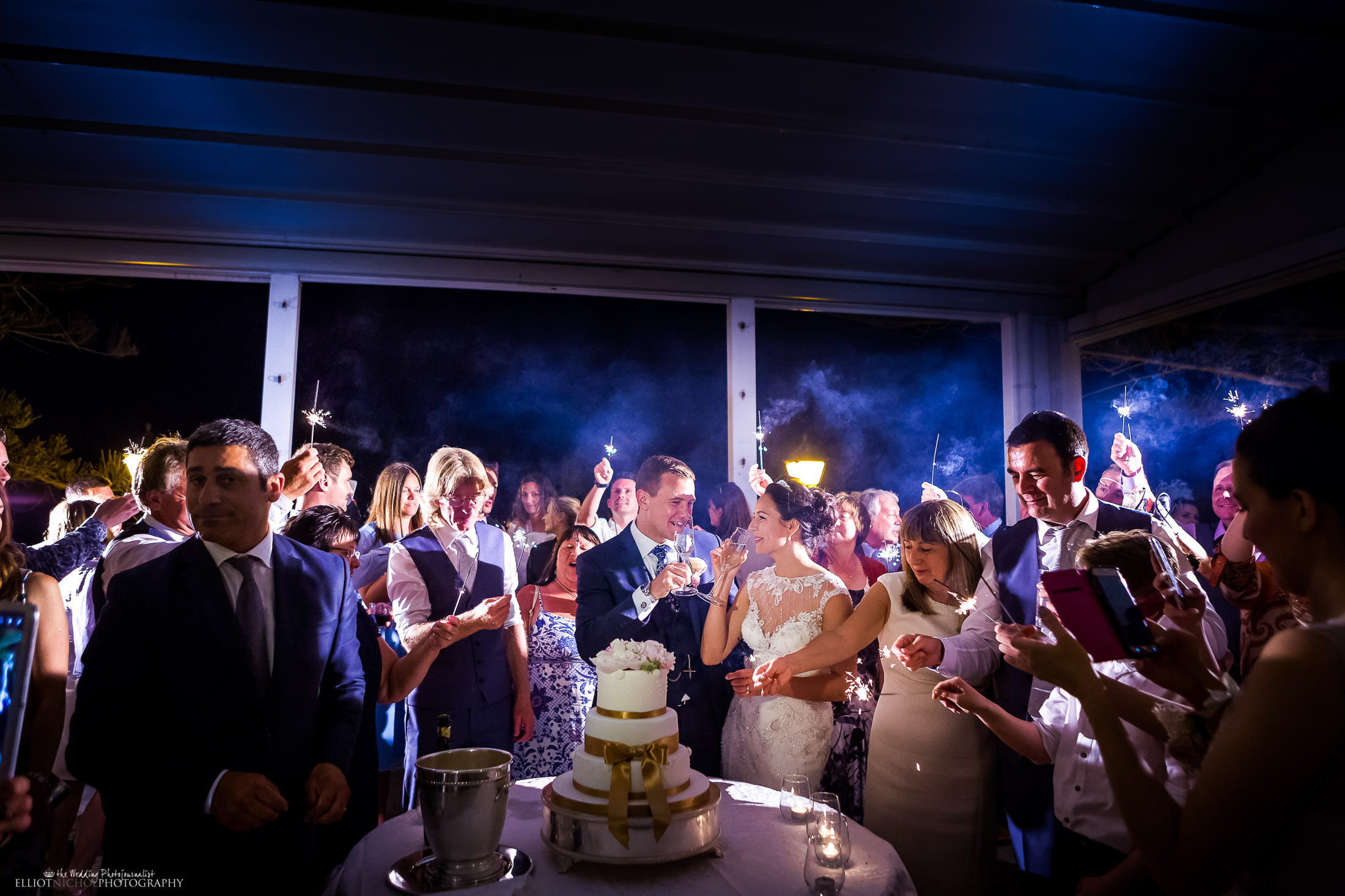 Bride and groom drink champagne together after cutting their wedding cake surrounded by friends and family. Photo by Elliot Nichol, the wedding photojournalist based in Newcastle Upon Tyne.