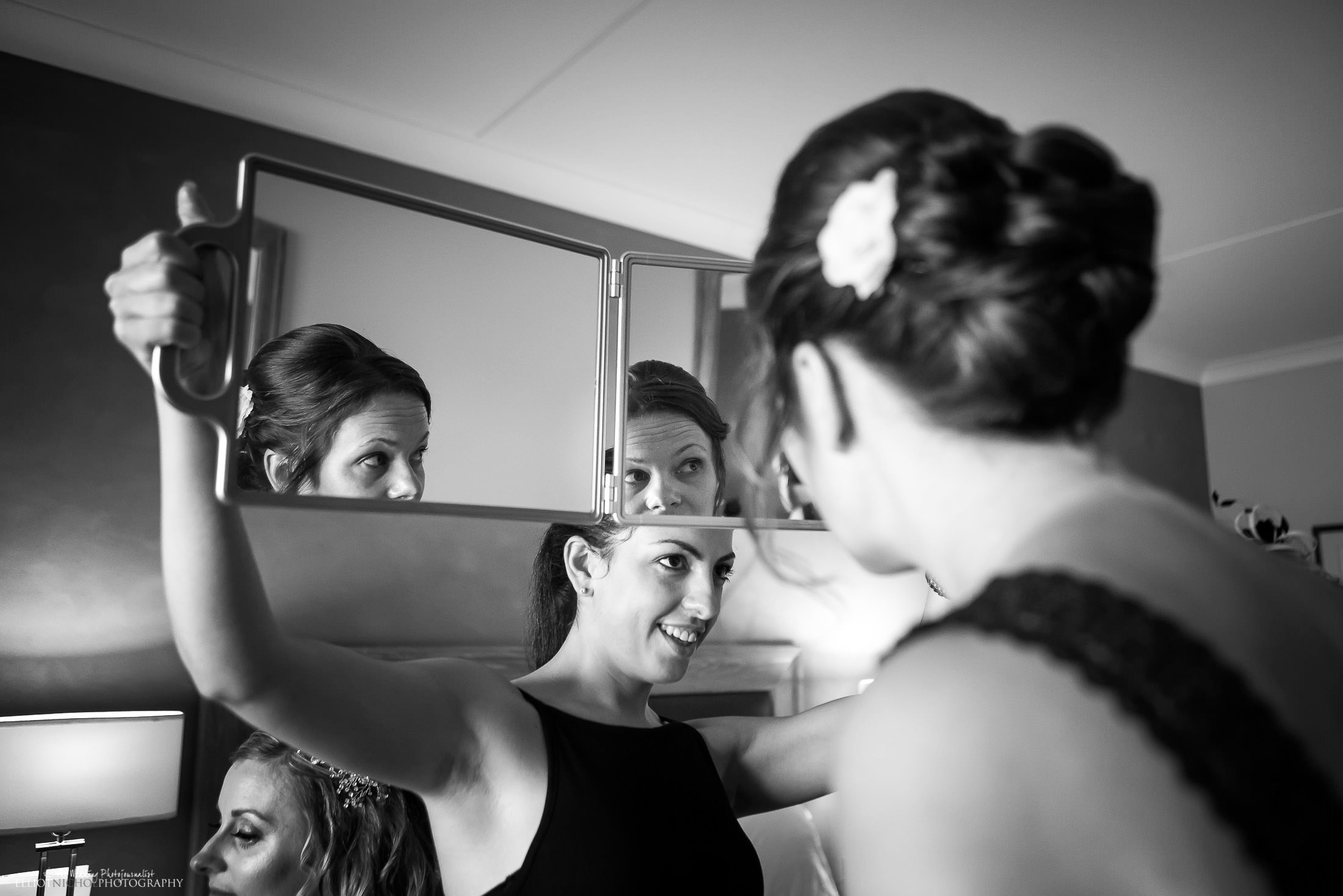 Hairstylist shows off her work to the bridesmaid. Photo by Northeast photographer that covers the UK and EU, Elliot Nichol.
