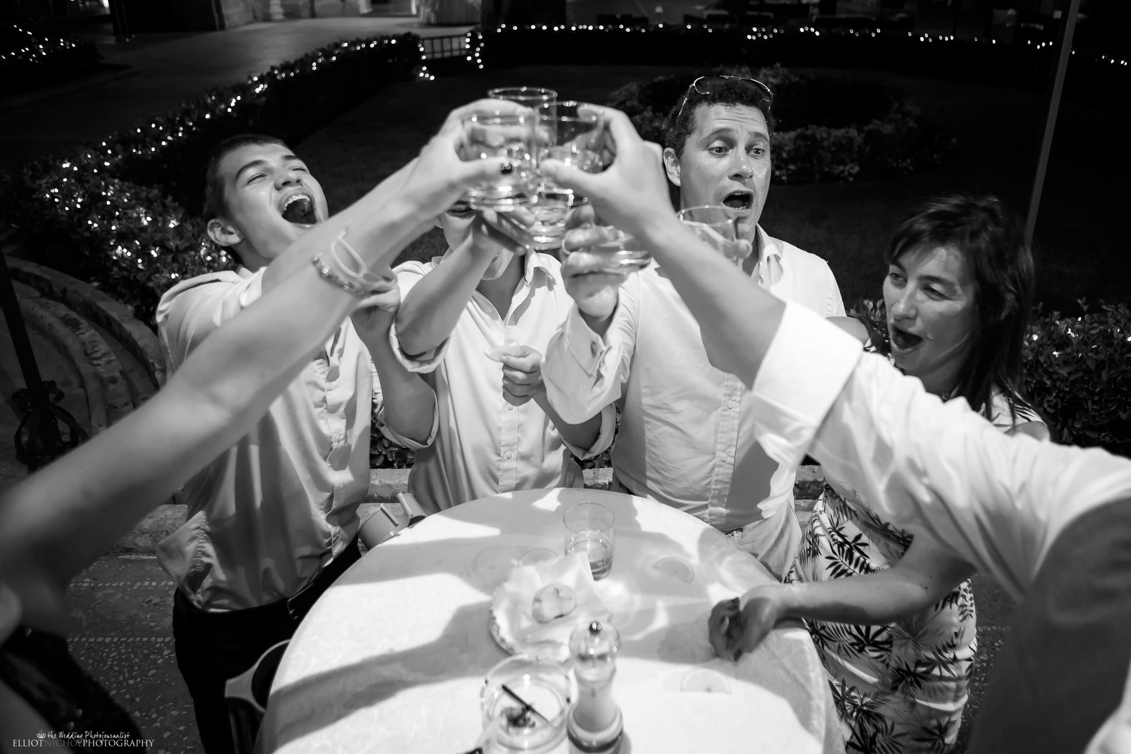 Wedding guests having fun while drinking shots during the wedding reception party. Photo by Elliot Nichol Photography.