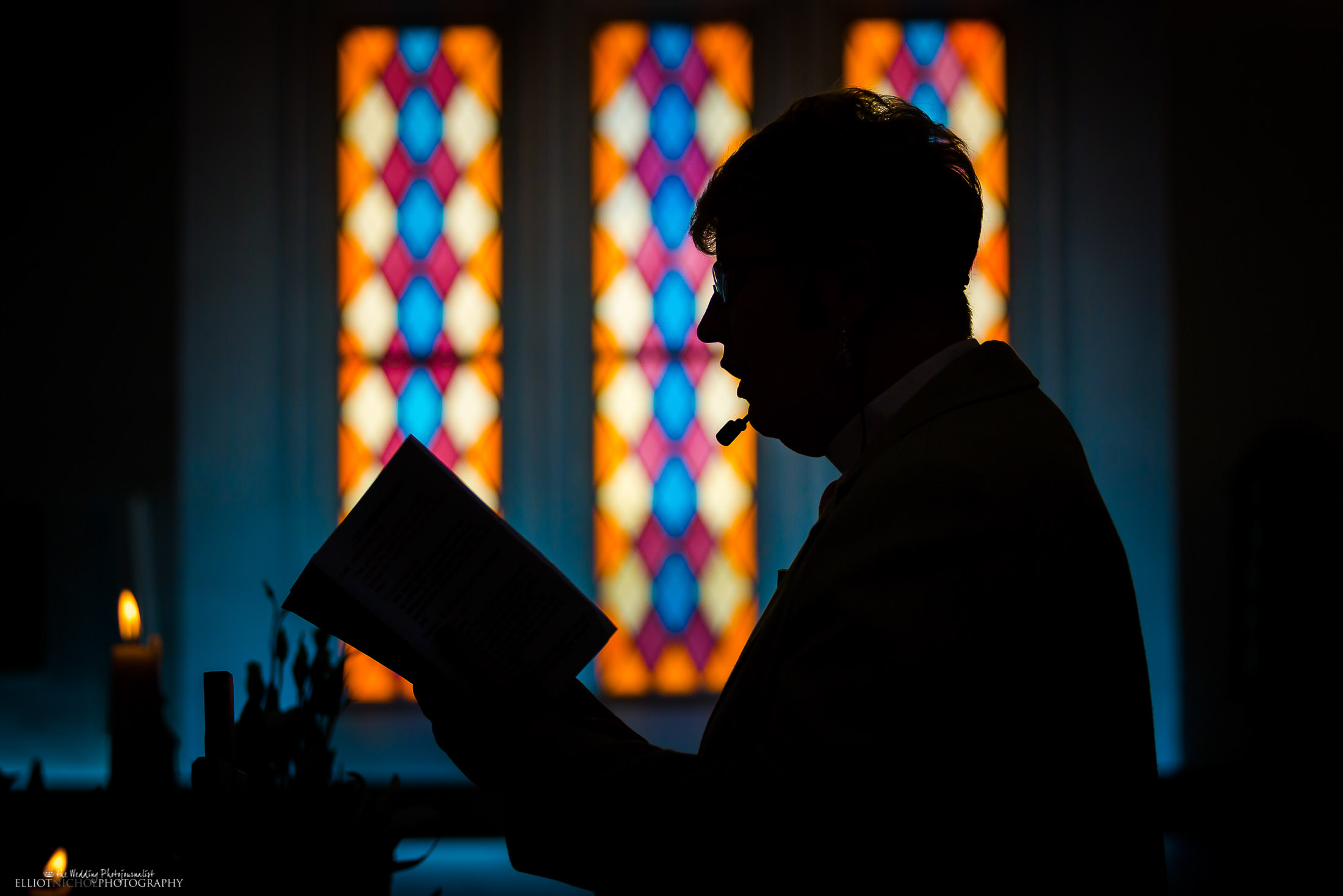 Silhouette of the Priest whist she reads during the church wedding ceremony. Photo by Elliot Nichol photography based in North East of England.