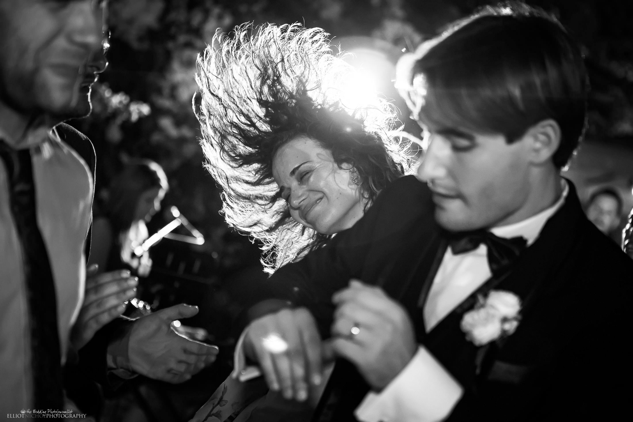 Wedding guests dancing wildly next to the groom. Photo by wedding photojournalist Elliot Nichol Photography.