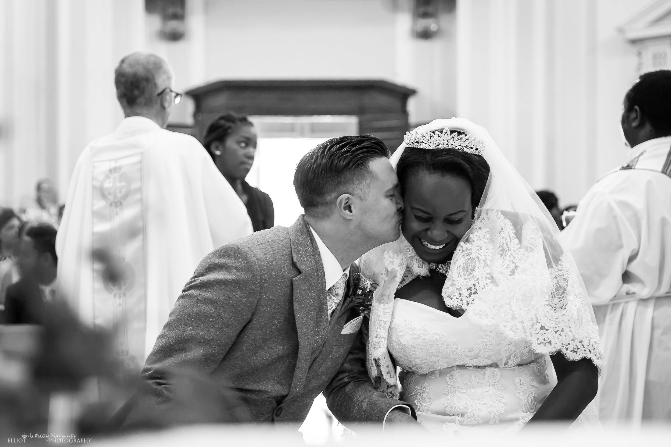 Groom steals a kiss during the church wedding ceremony. Photo by Elliot Nichol Photography.