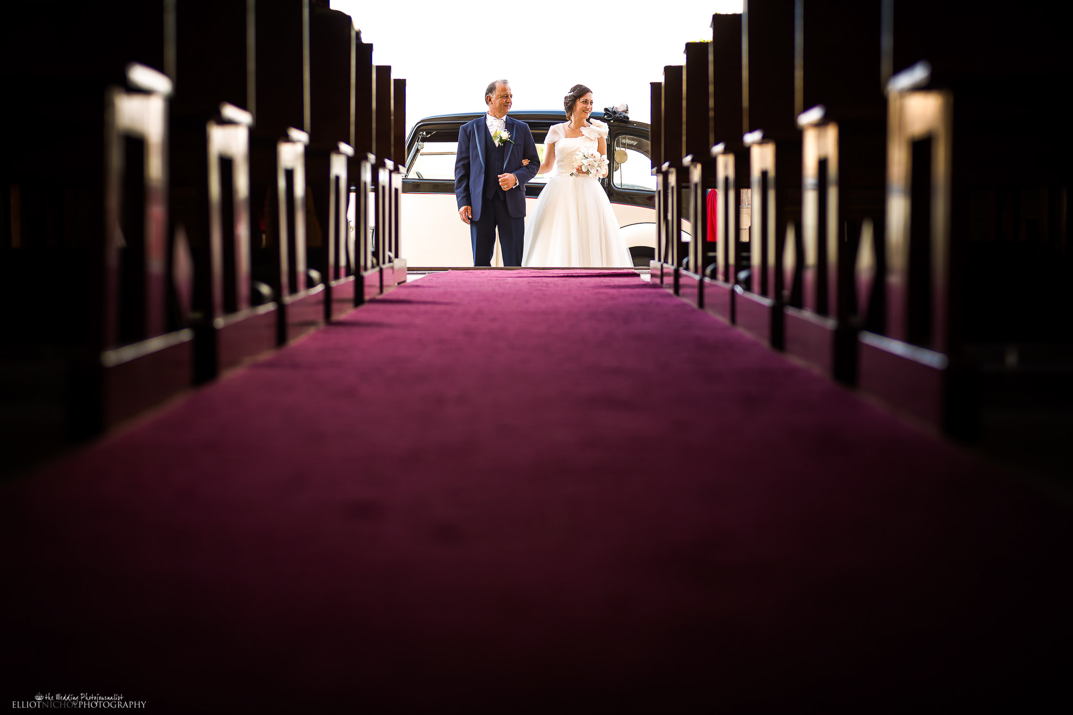 Bride with her father exit their vintage bridal car and wait outside the church before the ceremony. Photo by Elliot Nichol Photography.