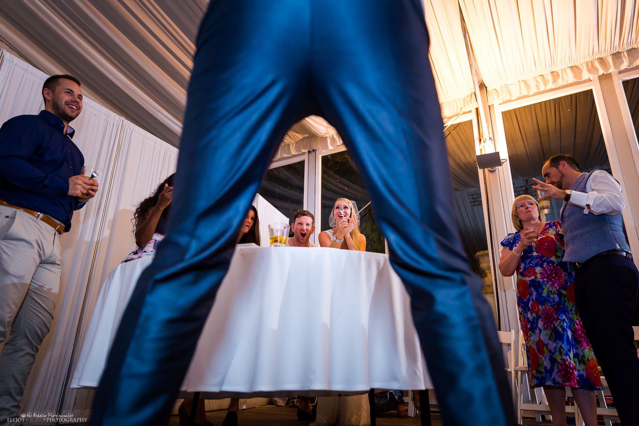 Bride ties to flick wedding cake off a folk into her wedding guests mouth. Photo by North East Wedding photojournalist Elliot Nichol.