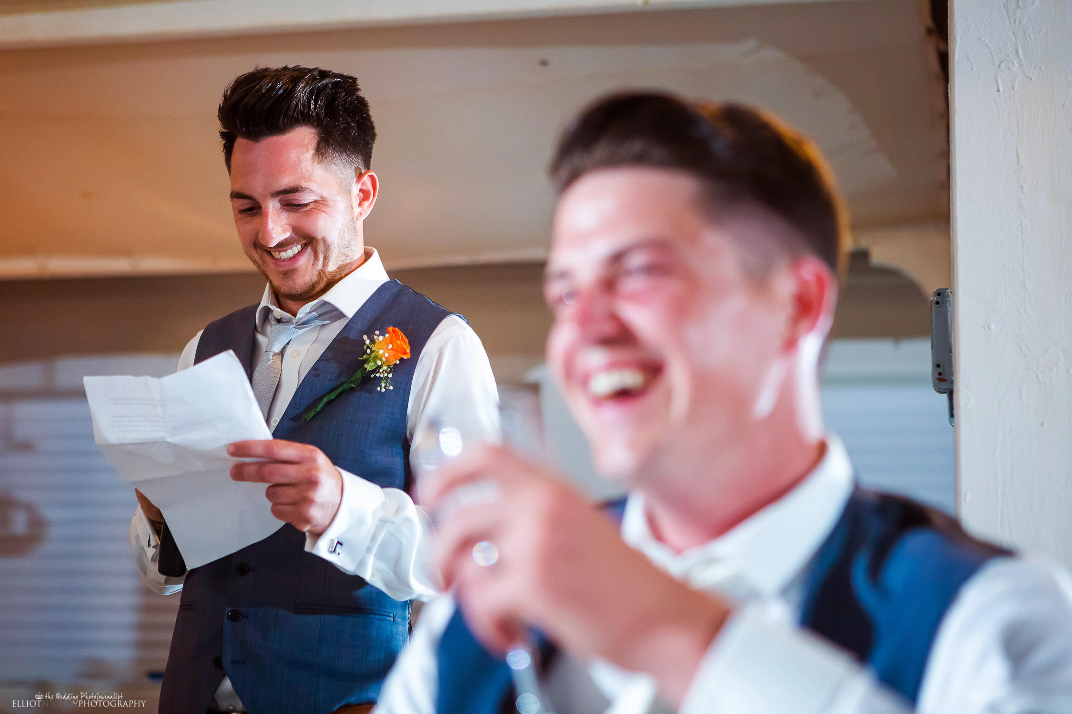 Best man makes the groom laugh during his wedding reception speech. Photo by Elliot Nichol Photography.