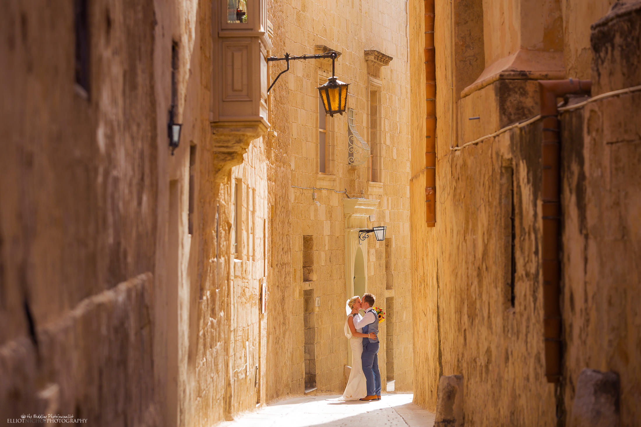 Bride and groom kissing in the medieval streets of Mdina in Malta. Photo by Elliot Nichol Photography.