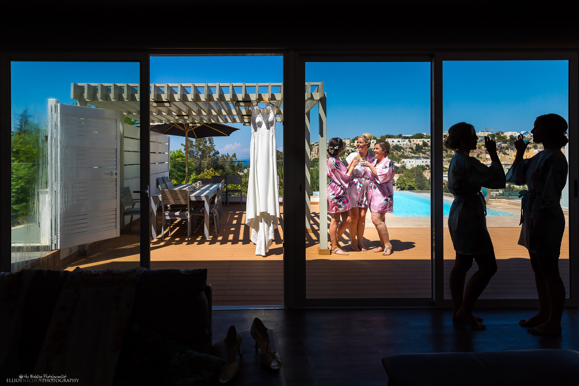 Bride and her bridesmaids enjoying some drinks at their destination wedding villa in the sun. Photography by Elliot Nichol.