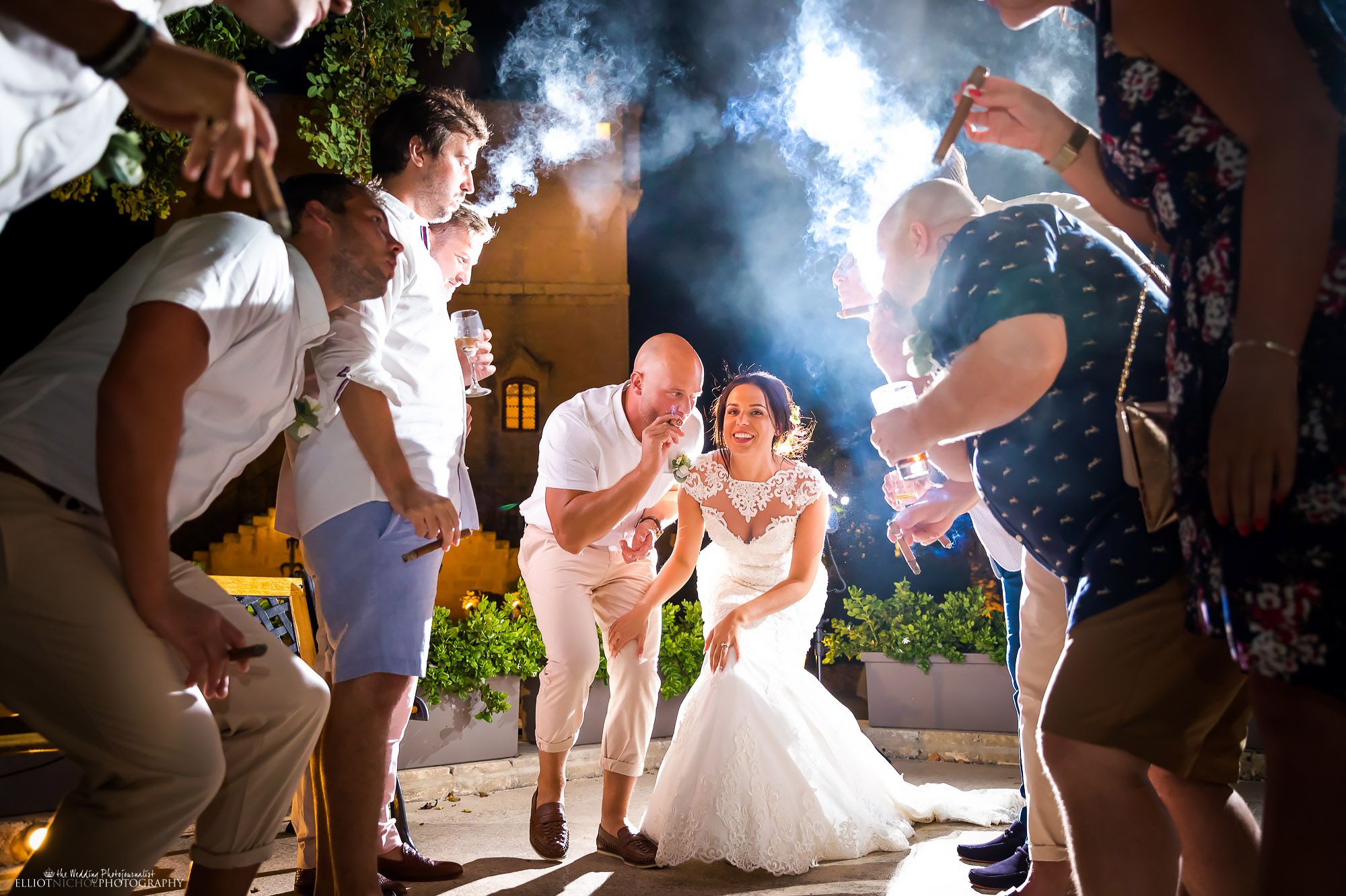 Bride and groom have some fun with their wedding guests who are smoking cigars and blow arch of smoke above them. Photo by Elliot Nichol Photography.