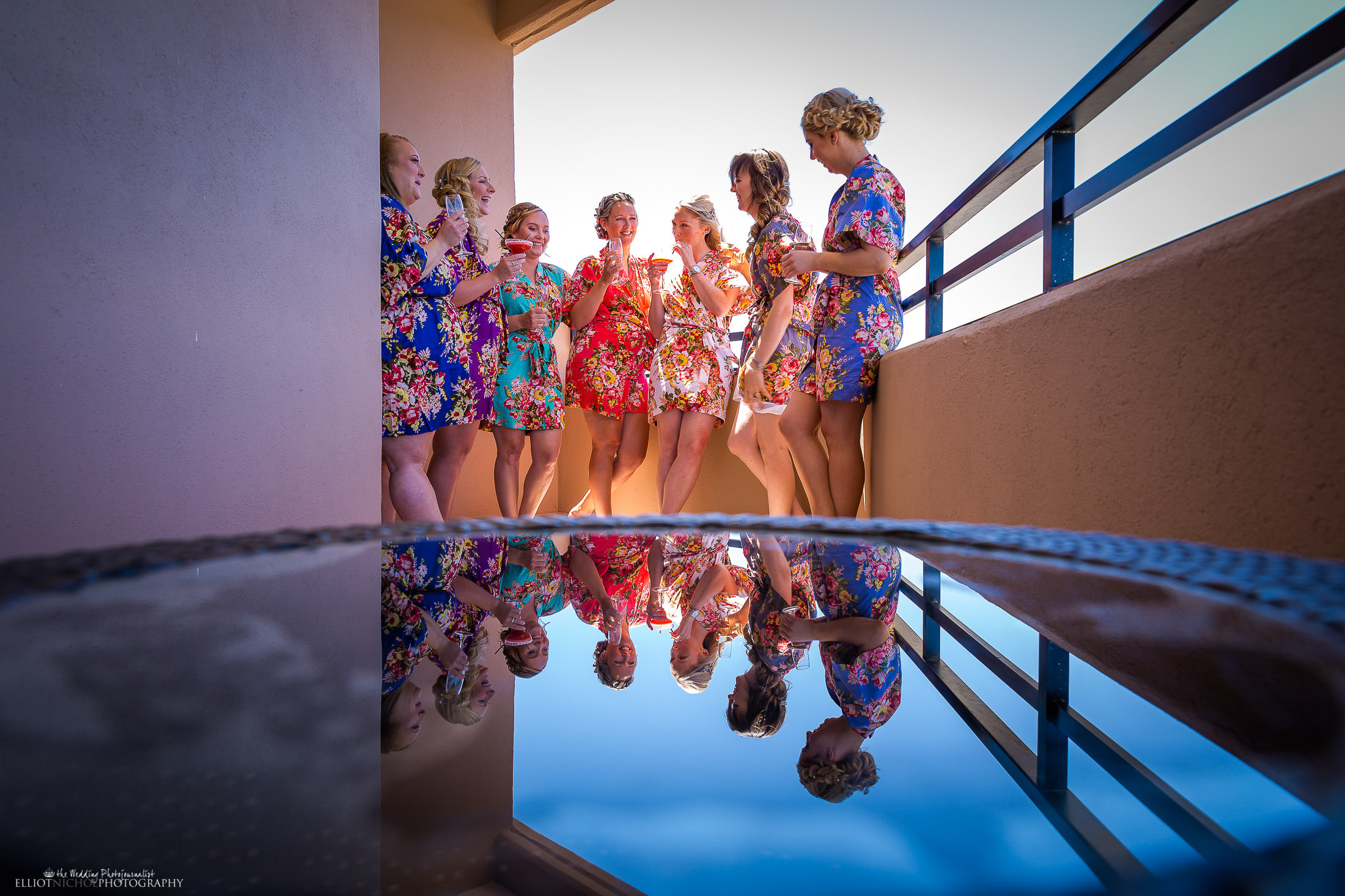 Bride with her bridesmaids having pre-ceremony drinks on the balcony. Photo by Elliot Nichol Photography.