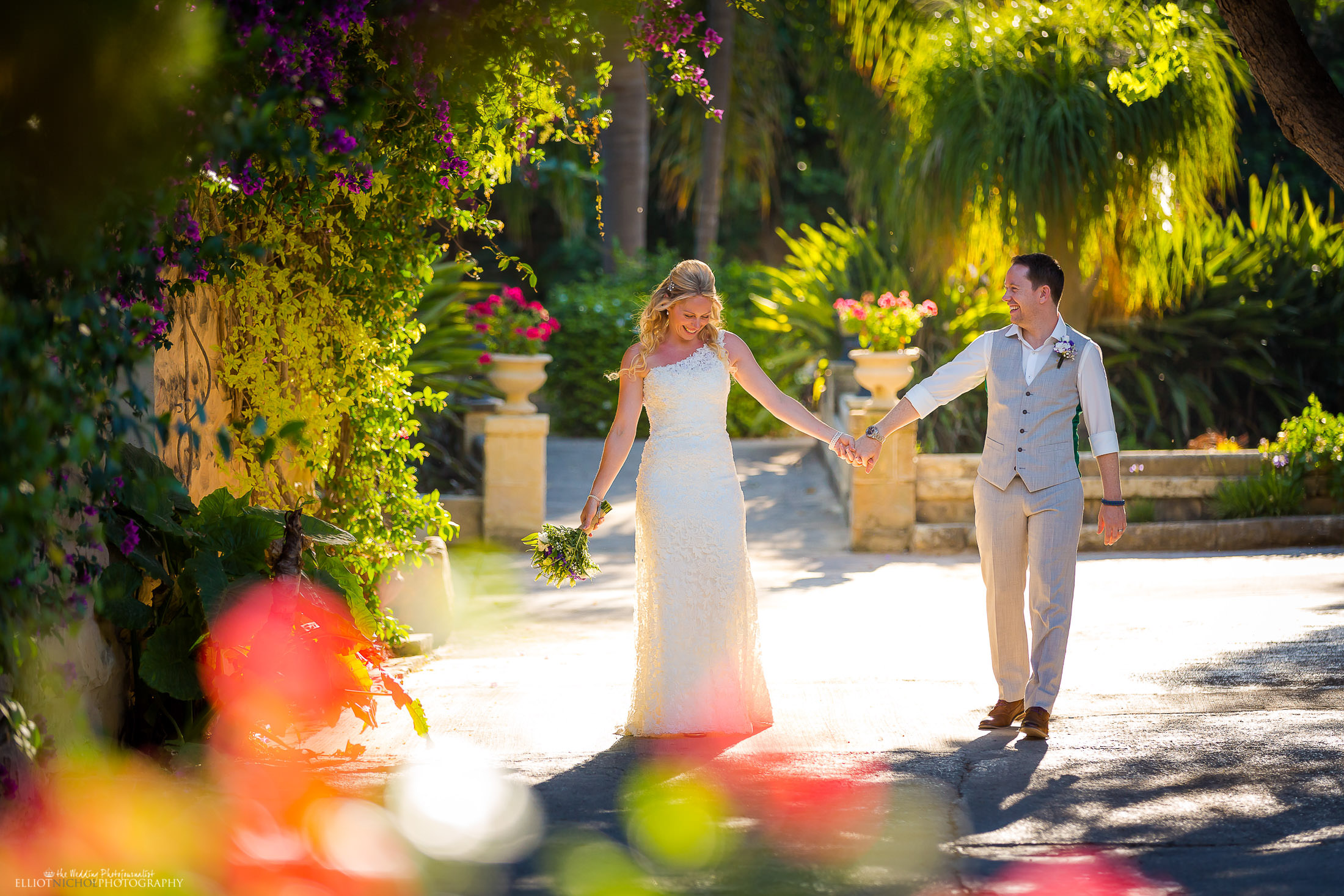 Bride and groom walk through their wedding venue gardens. Photo by Elliot Nichol Photography.