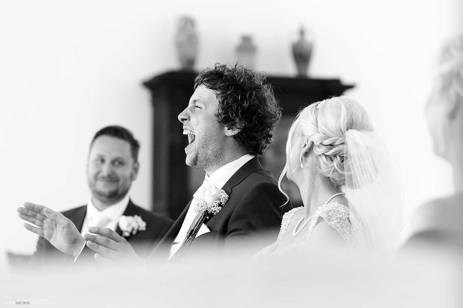 Groom in hysterics during his civil wedding ceremony. Fun Wedding photography by wedding photojournalist Elliot Nichol.