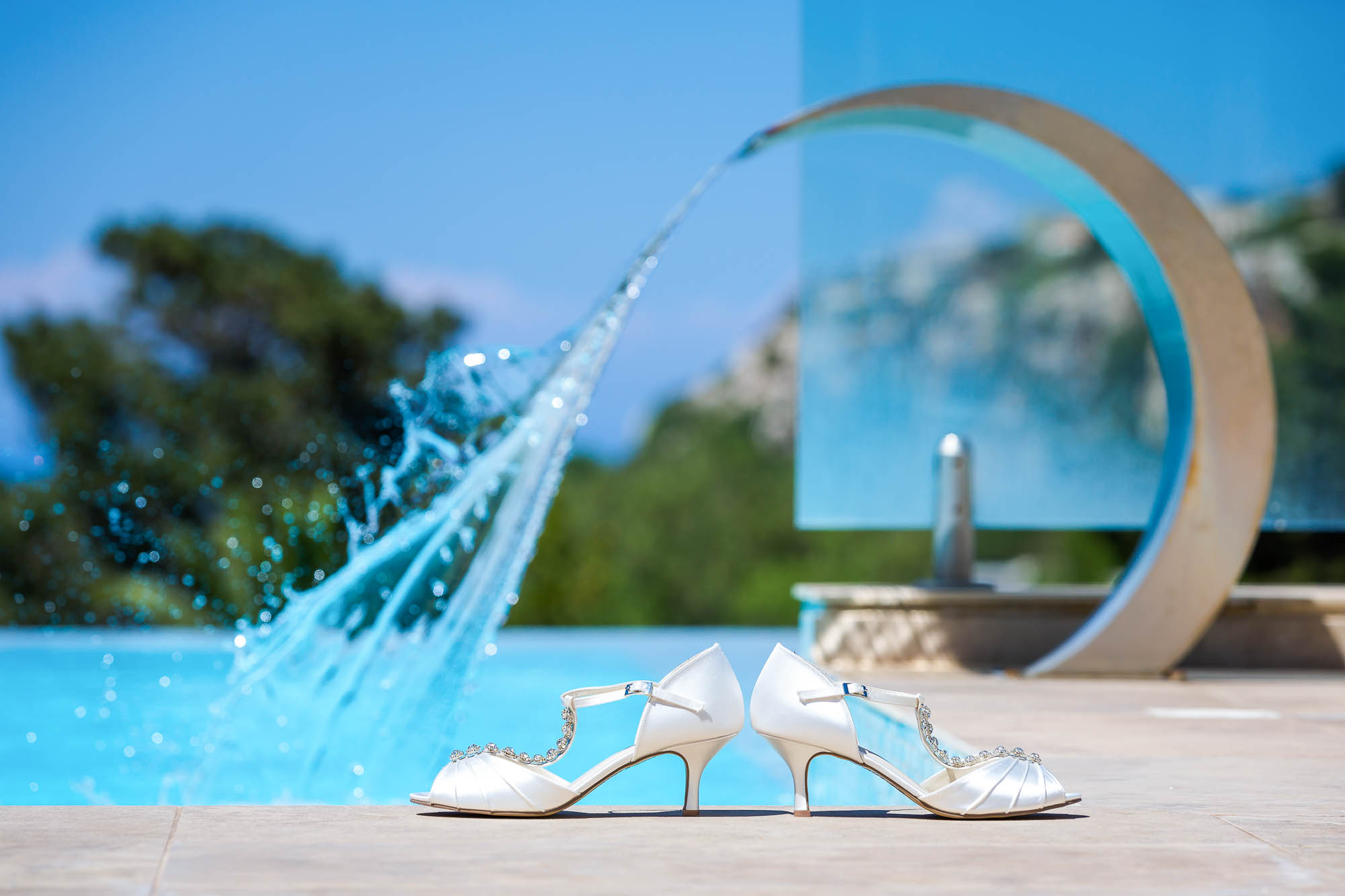Brides wedding shoes next to her destination vill's pool. Photo by Elliot Nichol Photography.