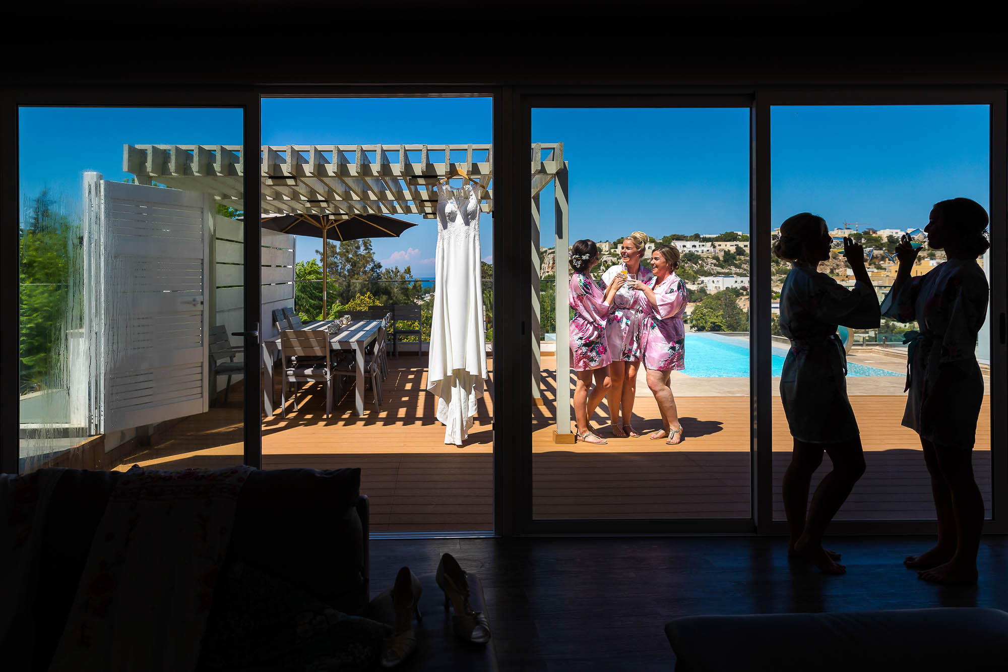 Bride enjoying a glass of champagne with her bridesmaids next to her villa's swimming pool. Photo by North East wedding photojournalist Elliot Nichol.