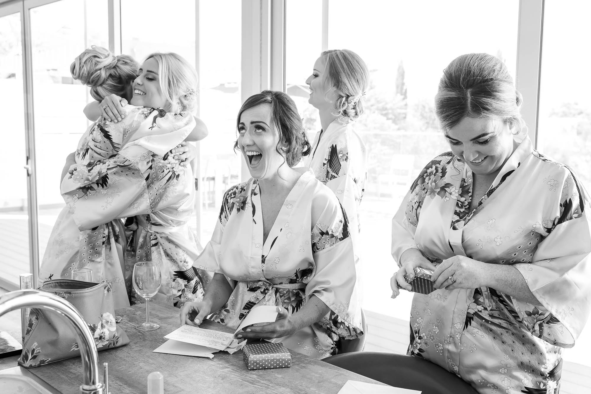 Bride giving her bridesmaids gifts before getting ready for her wedding. Photo by Elliot Nichol Photography.