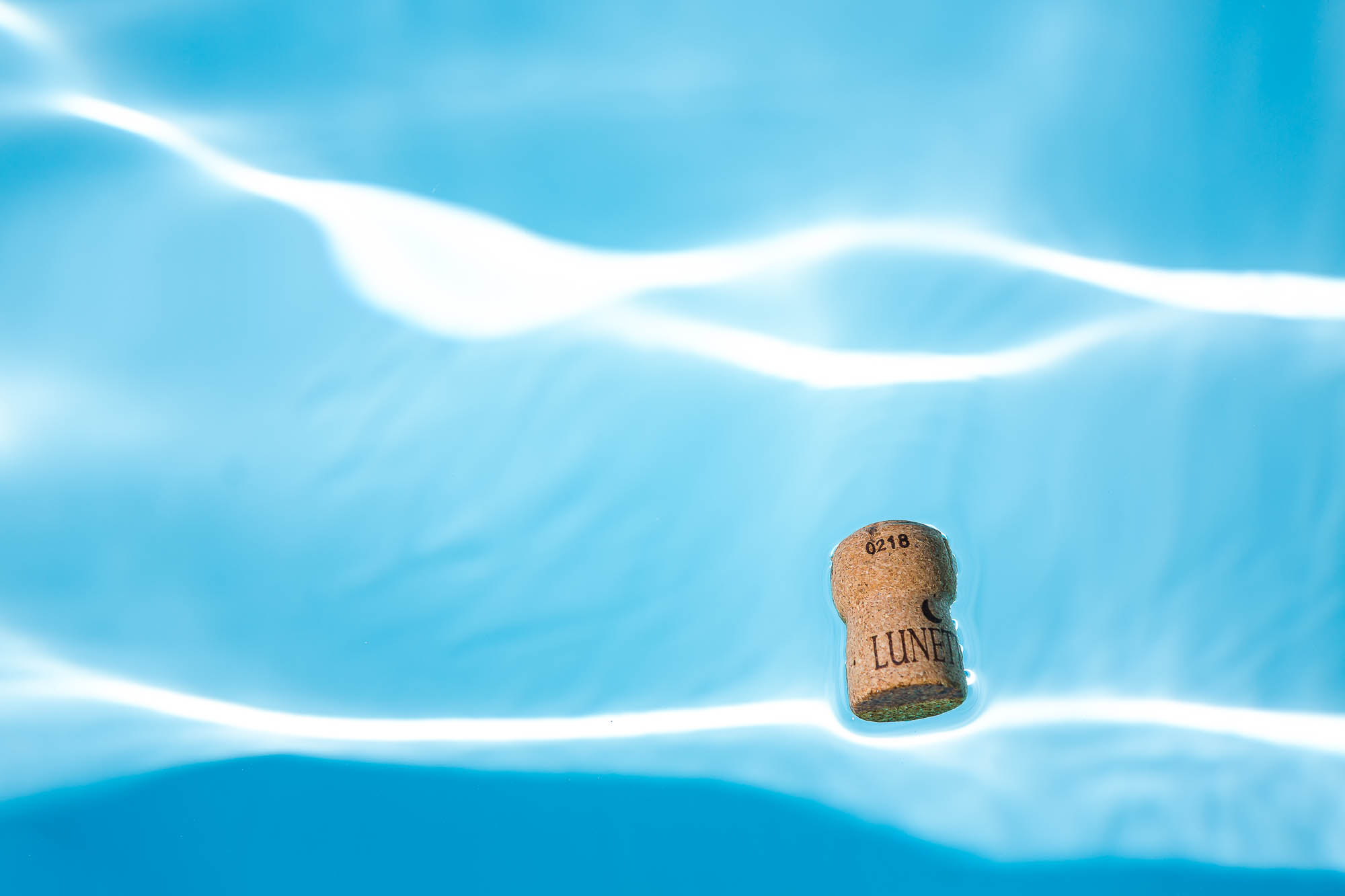 Champagne cork floating in the destination wedding swimming pool. Photo by Elliot Nichol Photography.