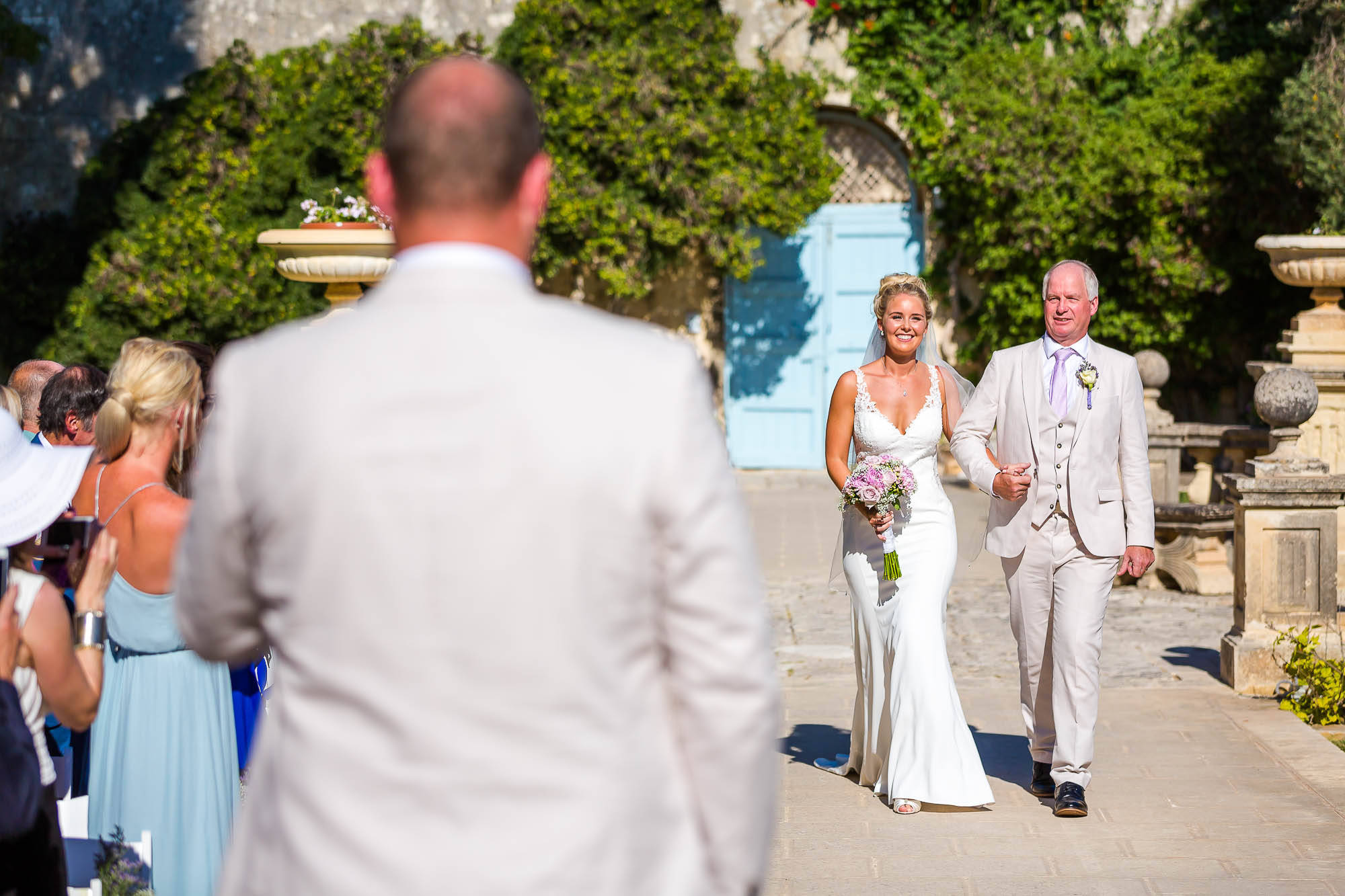 Bride arrives at the garden civil ceremony with her father. Photo by North East wedding photographer Elliot Nichol.