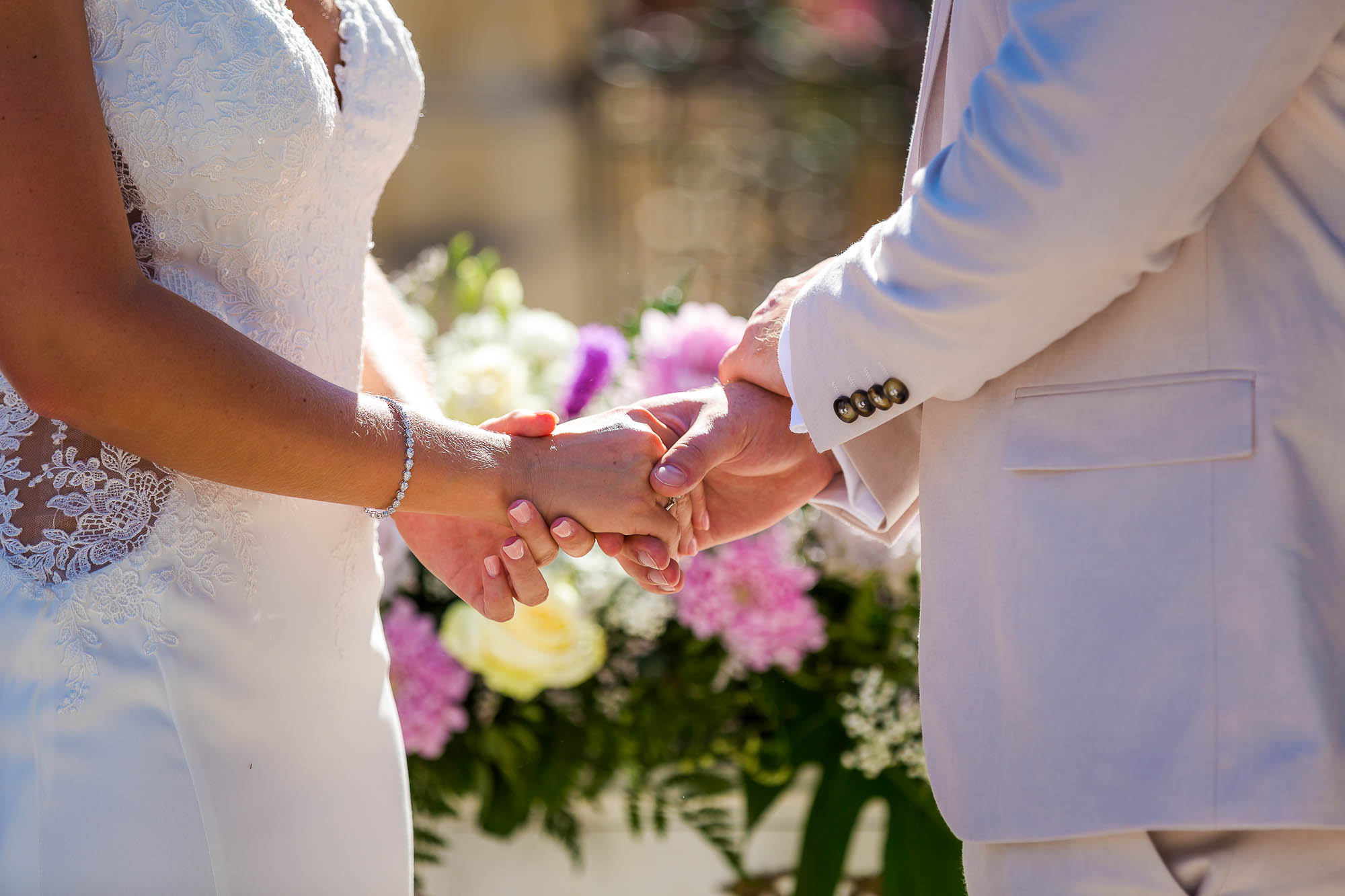Bride and groom hold hands during the wedding ceremony. Photo by Elliot Nichol Photography.