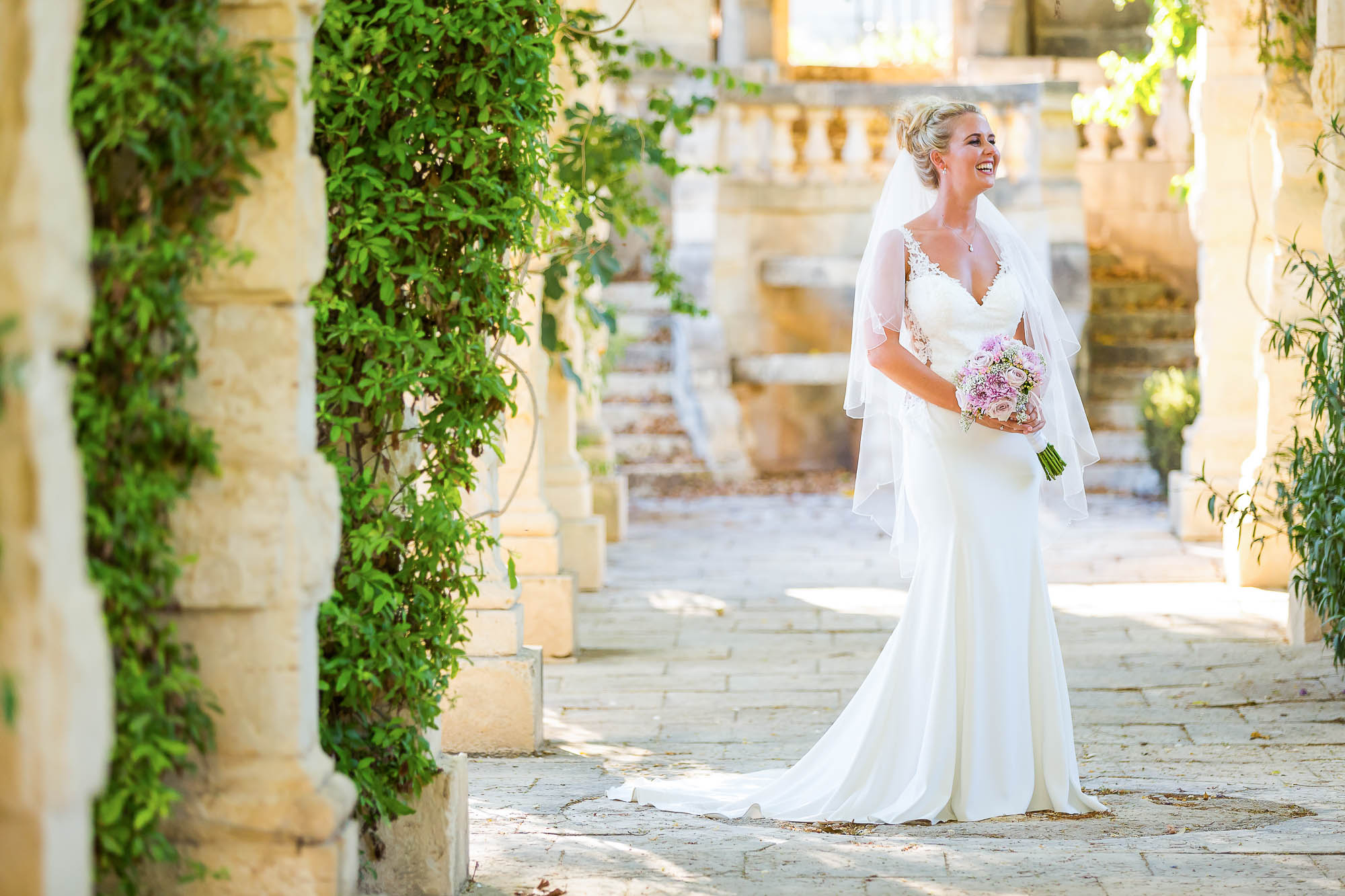 Portrait of the bride in the gardens of her wedding ceremony venue. Photo by destination photographer Elliot Nichol.