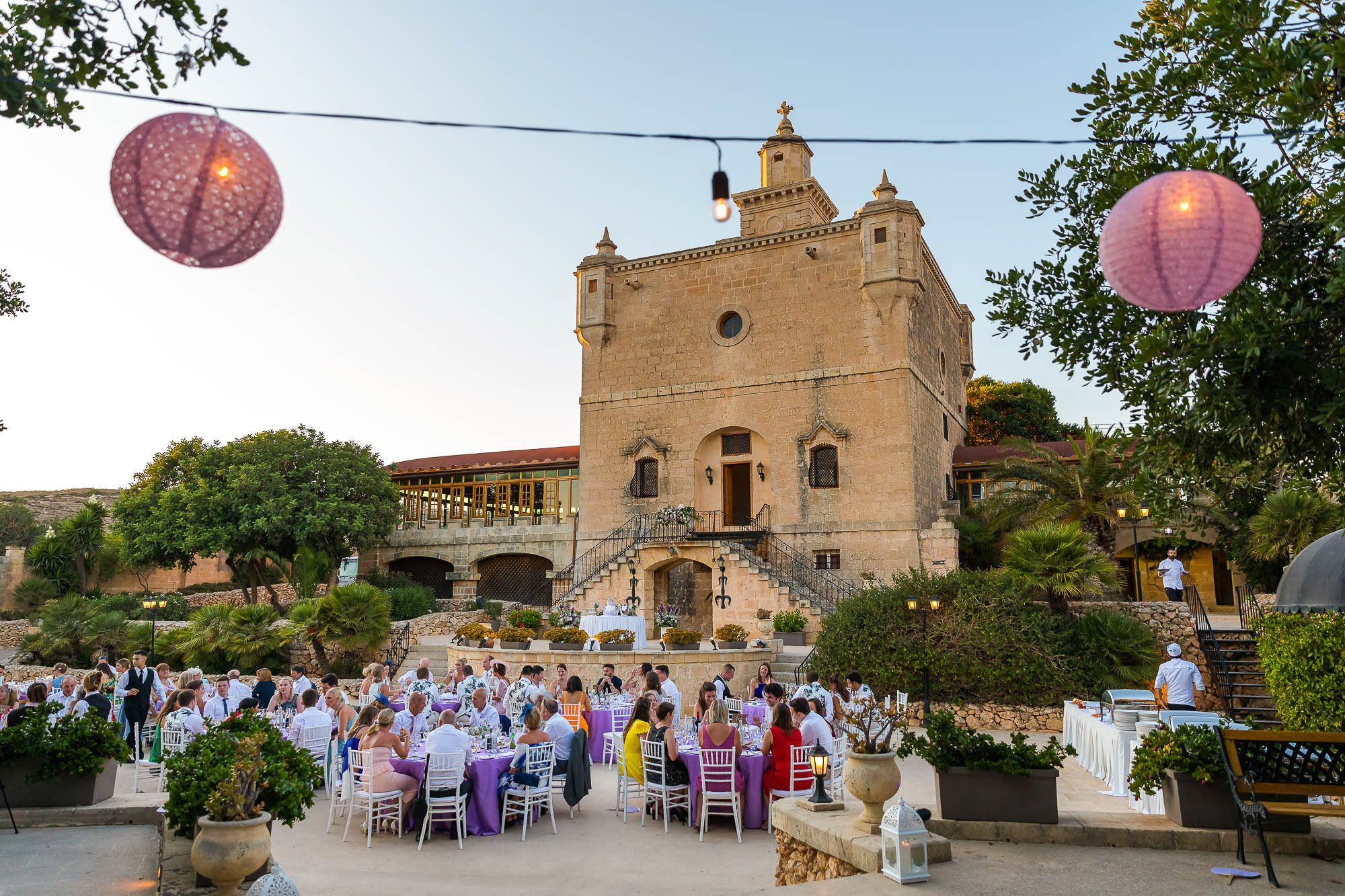 Wedding guests sit down to their wedding meal at Castello Zammitello in Malta. Destination wedding photographer Elliot Nichol.