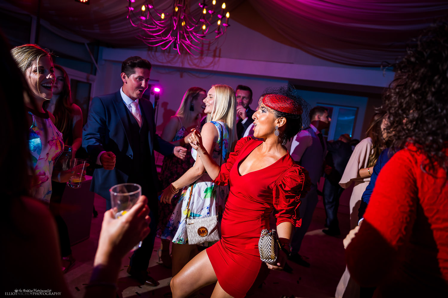Lady in red on the dance floor with the other wedding guests partying during the reception party. Photo by Elliot Nichol Photography.