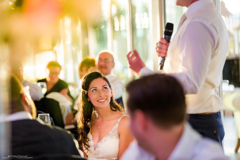 Bride enjoying her groom's wedding speech. Photo by Elliot Nichol Photography.