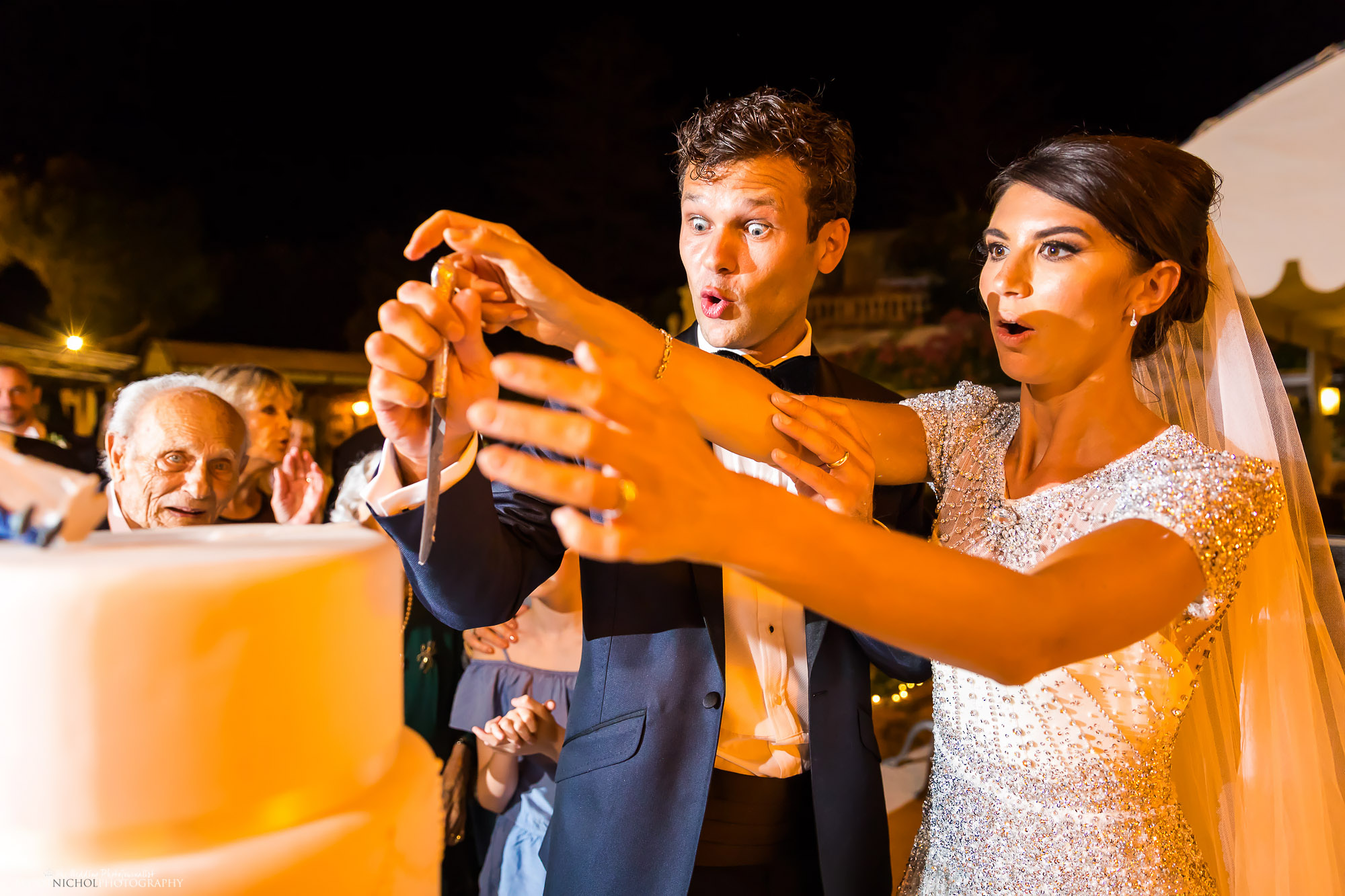 Funny expression on the bride and grooms face during their wedding cake cutting as their cake topper falls off. Photo by Elliot Nichol Photography based in Newcastle Upon Tyne.