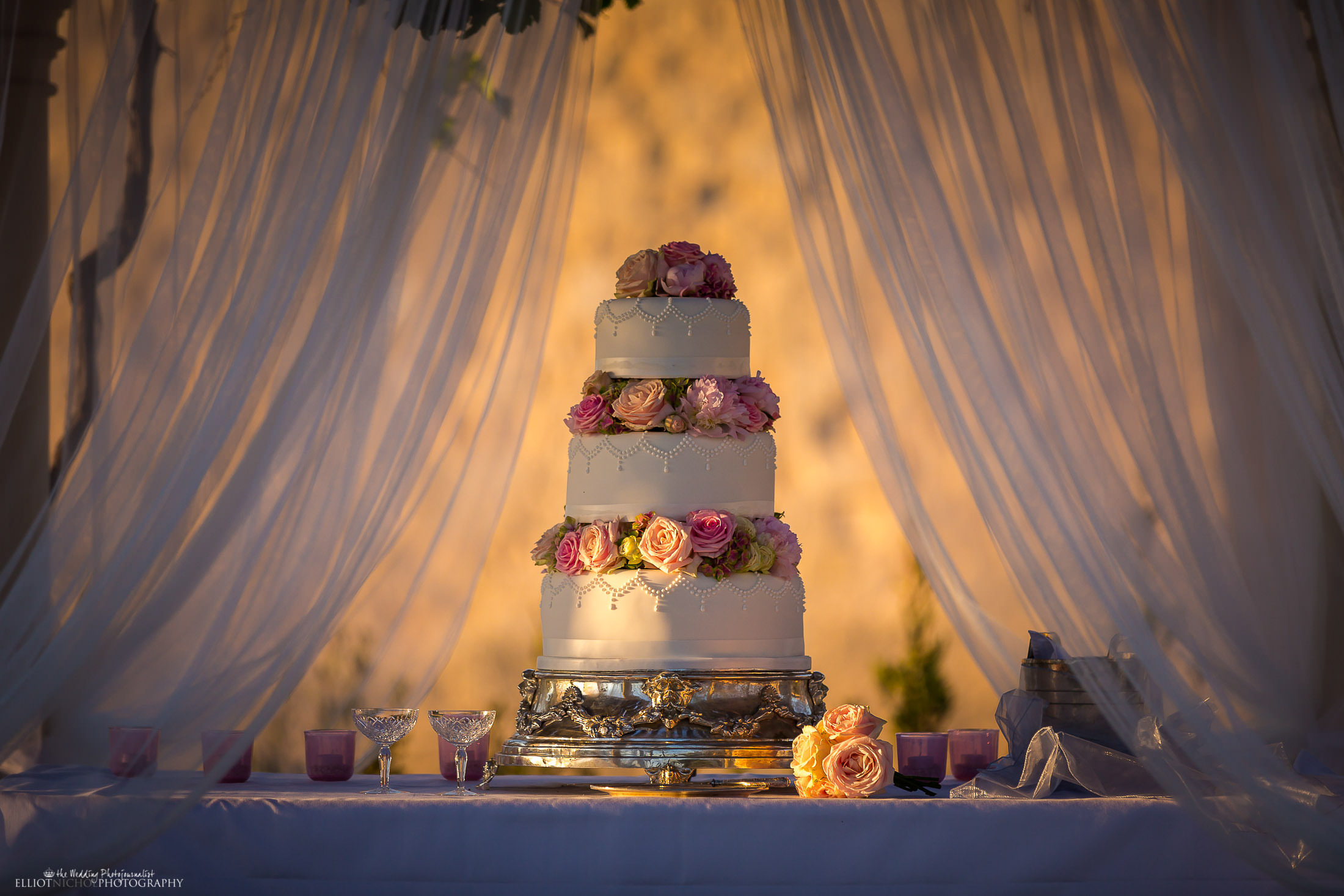 Three tier wedding cake filled with roses. Photo by Elliot Nichol Photography.