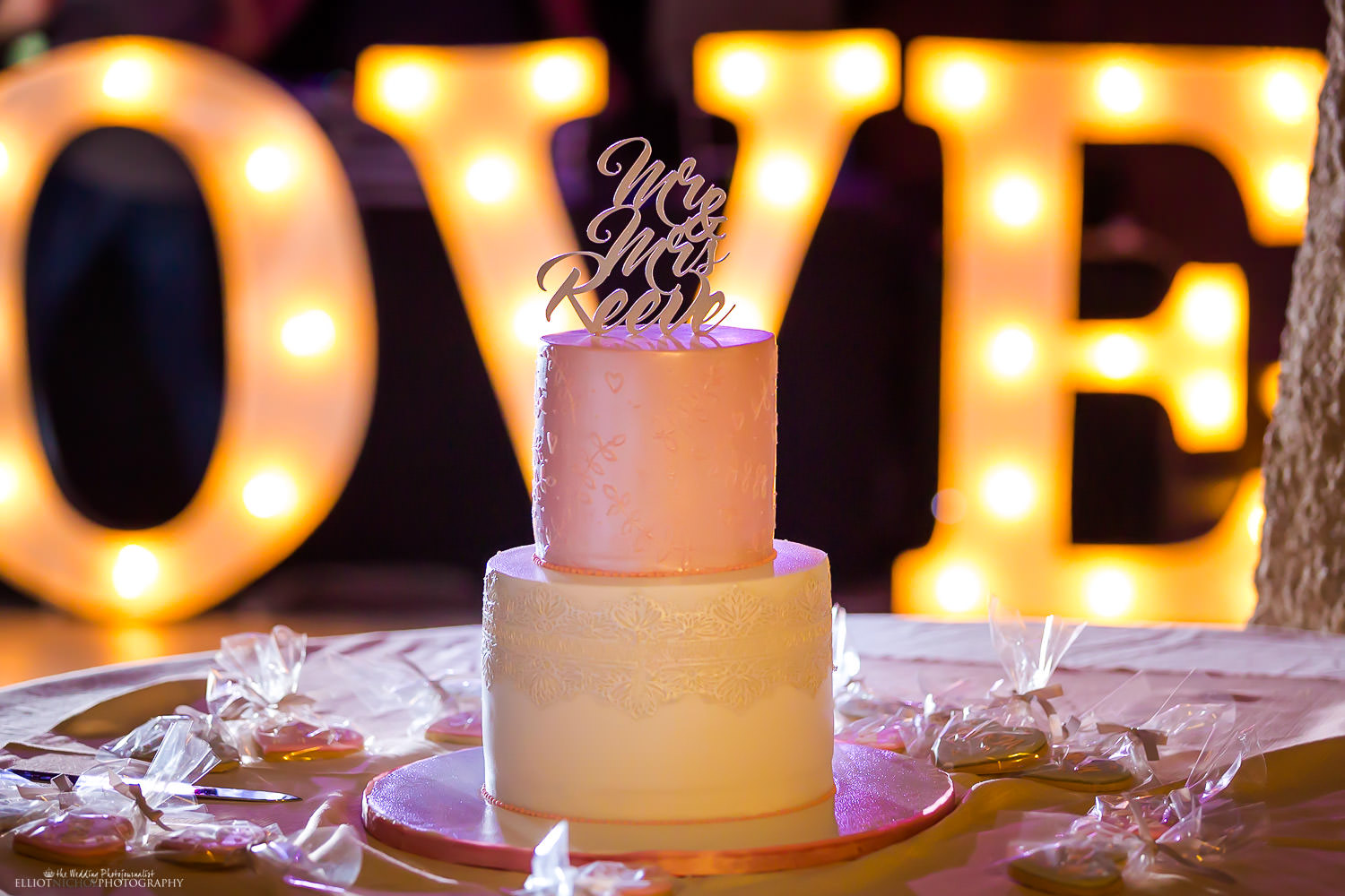 Wedding cake with Mr & Mrs wedding cake topper and love sign behind. Photo by Newcastle wedding photographer.