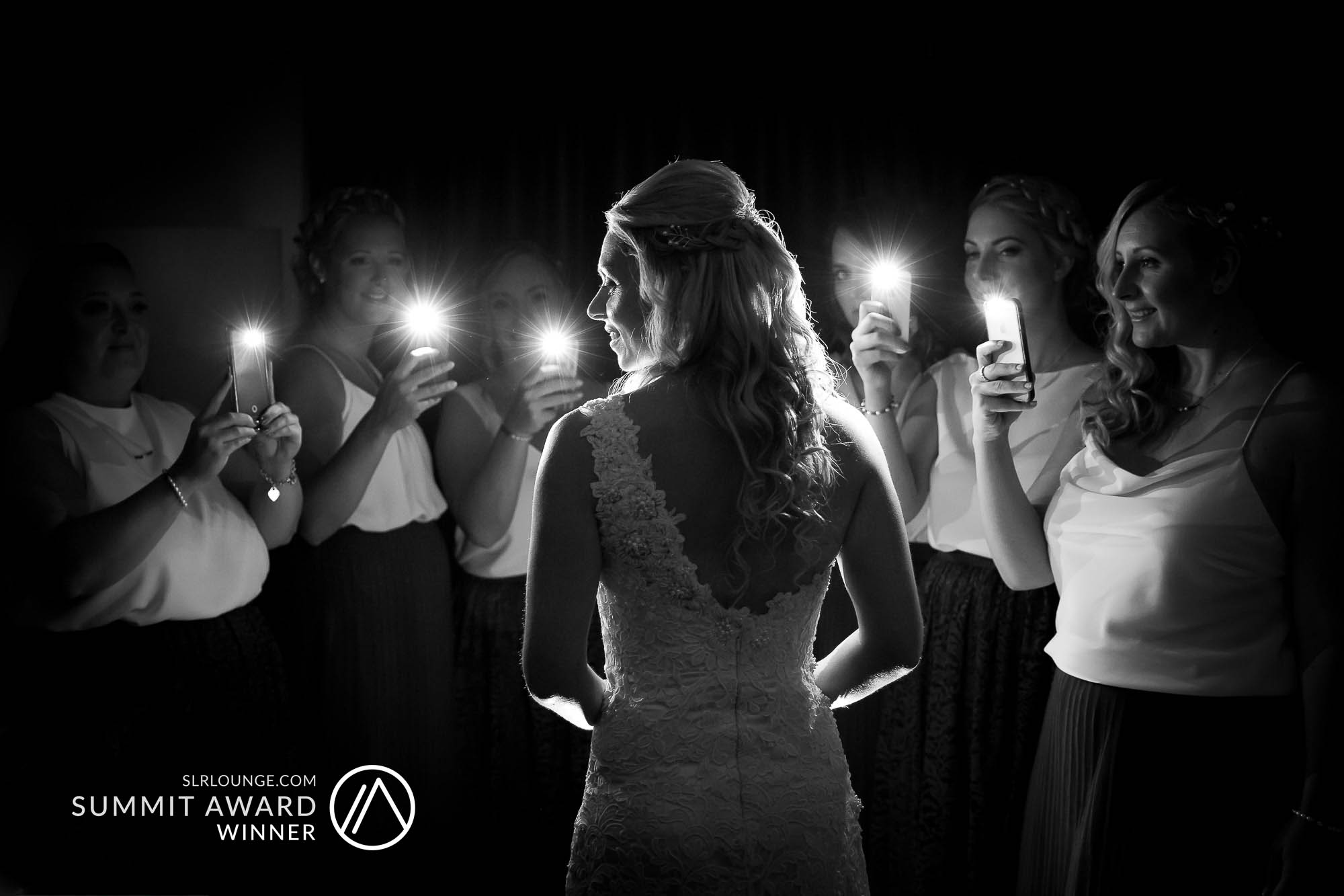 SLR Lounge's Summit Award winning image. Creative wedding photograph of the bride being light up by her bridesmaids taking photos of her using their mobile phones. Photo by Newcastle based wedding photographer, Elliot Nichol, photographing weddings across the UK and the EU.