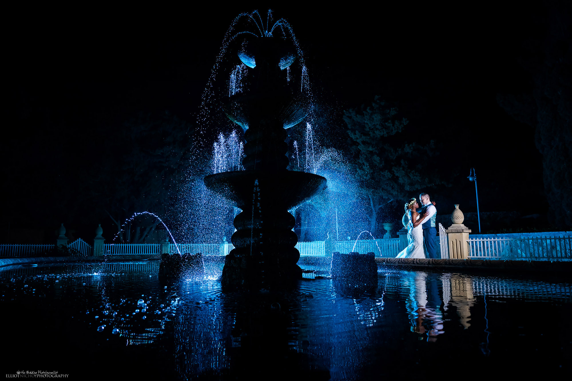 Bride and groom's evening wedding day portrait next to their wedding venue's water fountain. Photo by Elliot Nichol Photography.