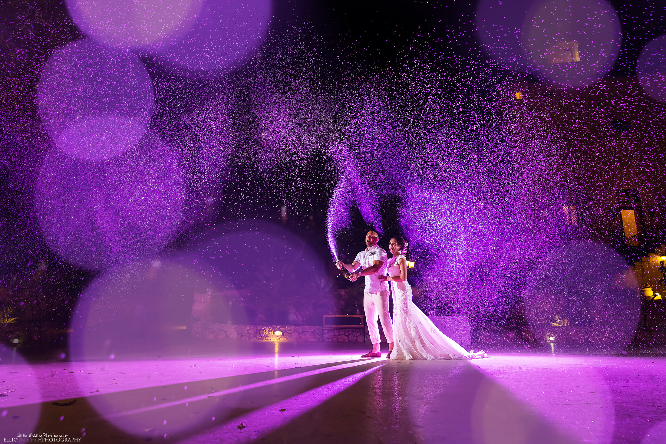 North East couple spraying champagne during their wedding reception. Photo by Wedding Photojournalist Elliot Nichol Photography based in Newcastle Upon Tyne.
