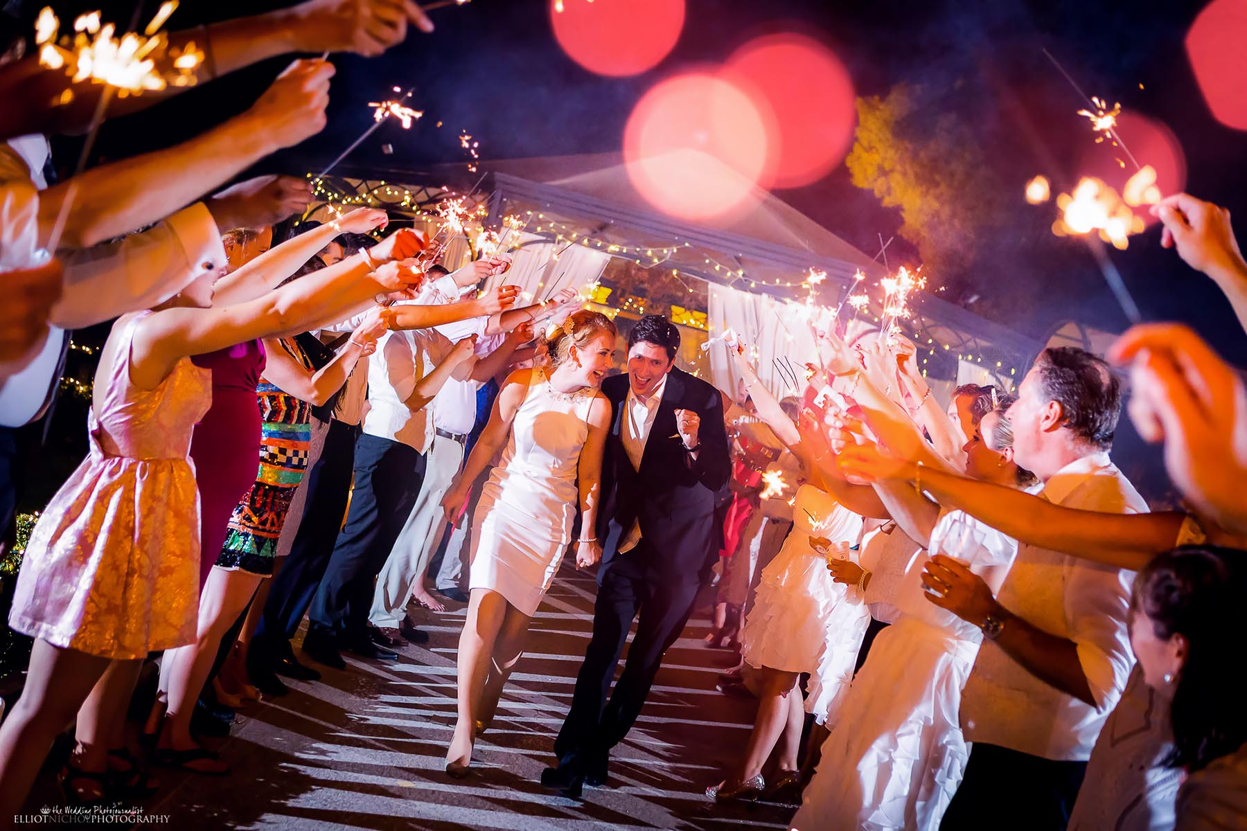 Newcastle Upon Tyne couple leaving their wedding reception venue through a sparking farewell from their guests holding sparklers. Photo by North East wedding photographer Elliot Nichol.