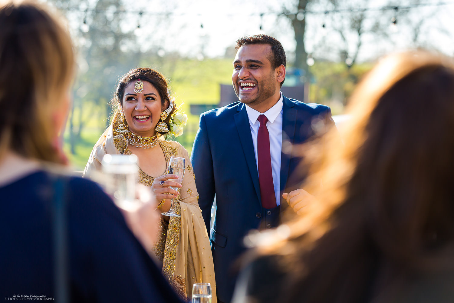 Candid moment of Asian couple enjoying drinks with their engagement party guests at Vallum Farm. Photo by North East wedding and engagement photographer Elliot Nichol.