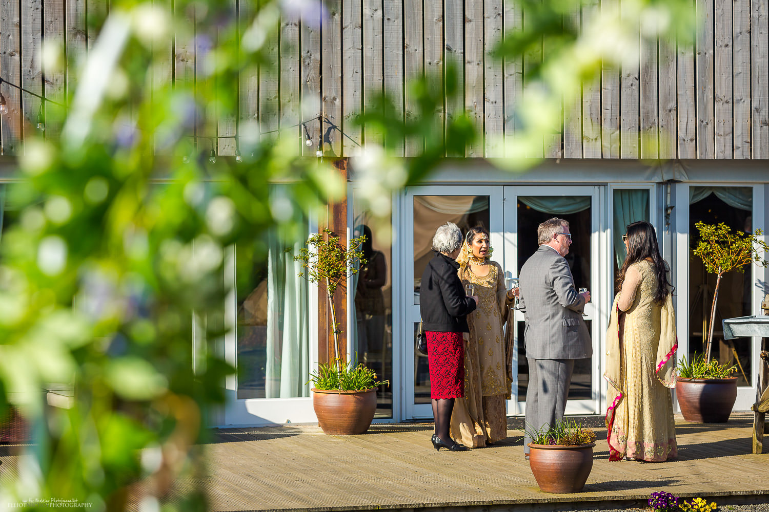 Guests and bride relaxing with drinks at Vallum Farm.