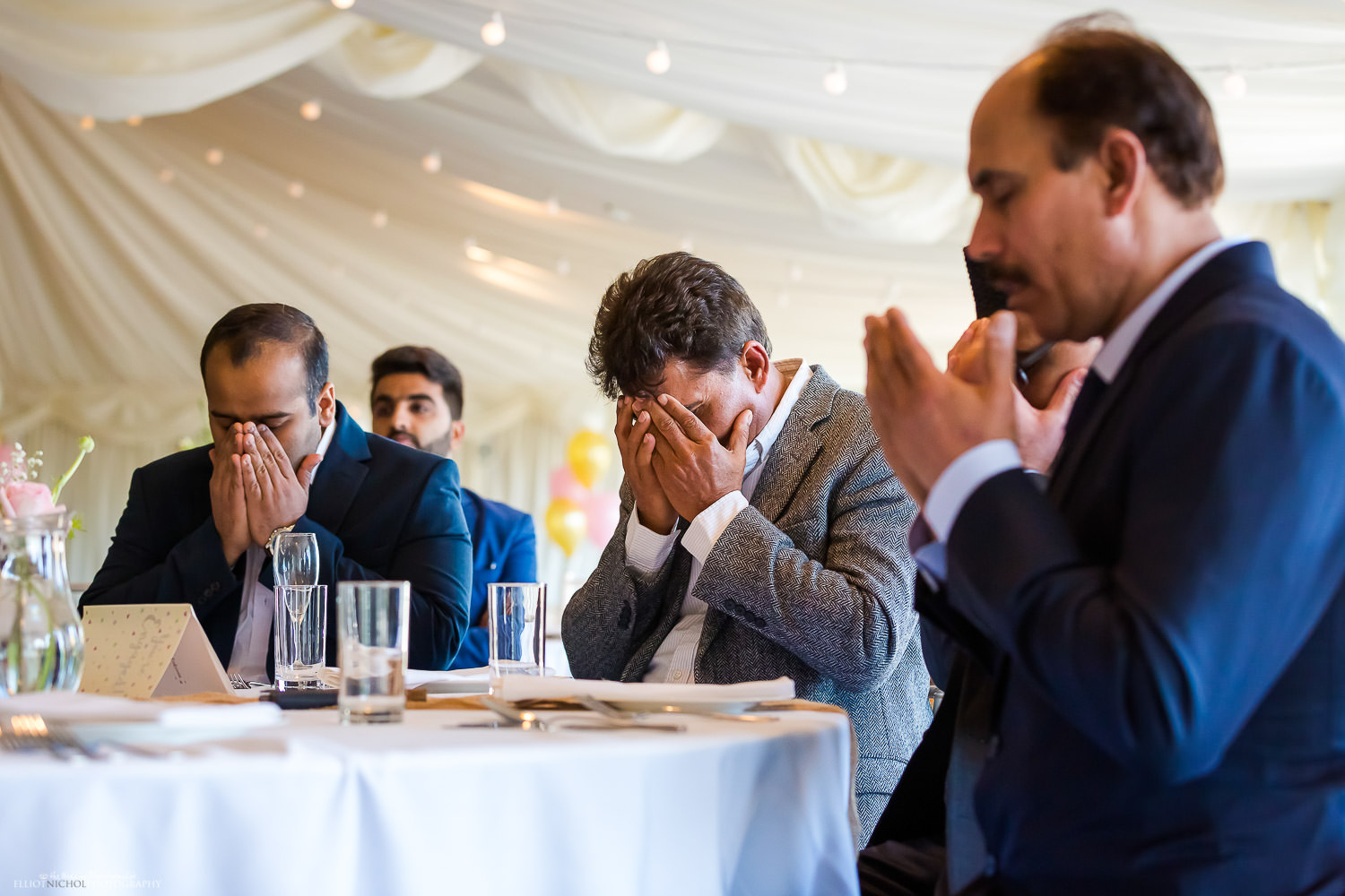 Silent pray at asian engagement party. Photo by North East wedding photojournalist Elliot Nichol.