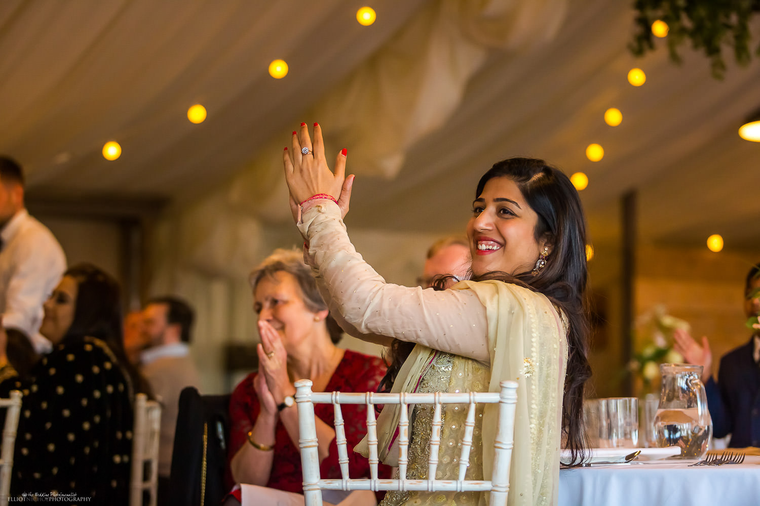 Party guest enjoying the speeches. Candid photo by wedding photojournalist Elliot Nichol.
