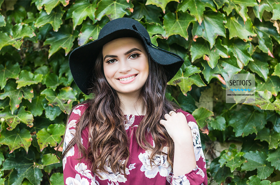 senior girl in wide-brimmed hat with leaves at Loring Park in Minneapolis for senior photos