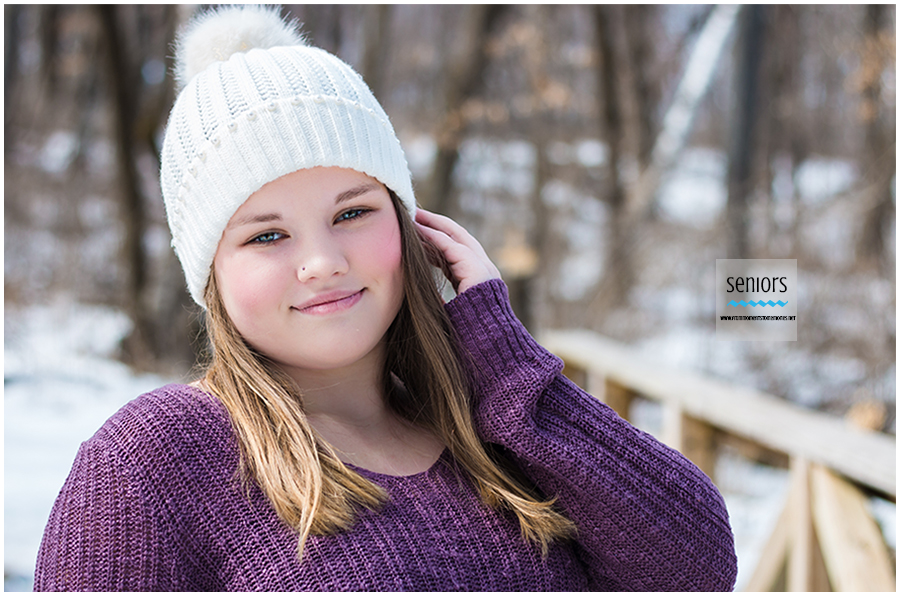 girl taking senior photos in sweater and hat in the winter at Woodland Trails Park in Elk River, Minnesota