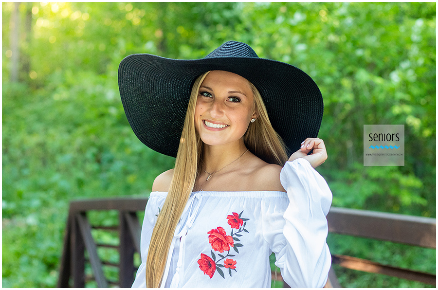 teenage girl with summer dress and hat getting her senior portraits taken at henry's woods park in rogers