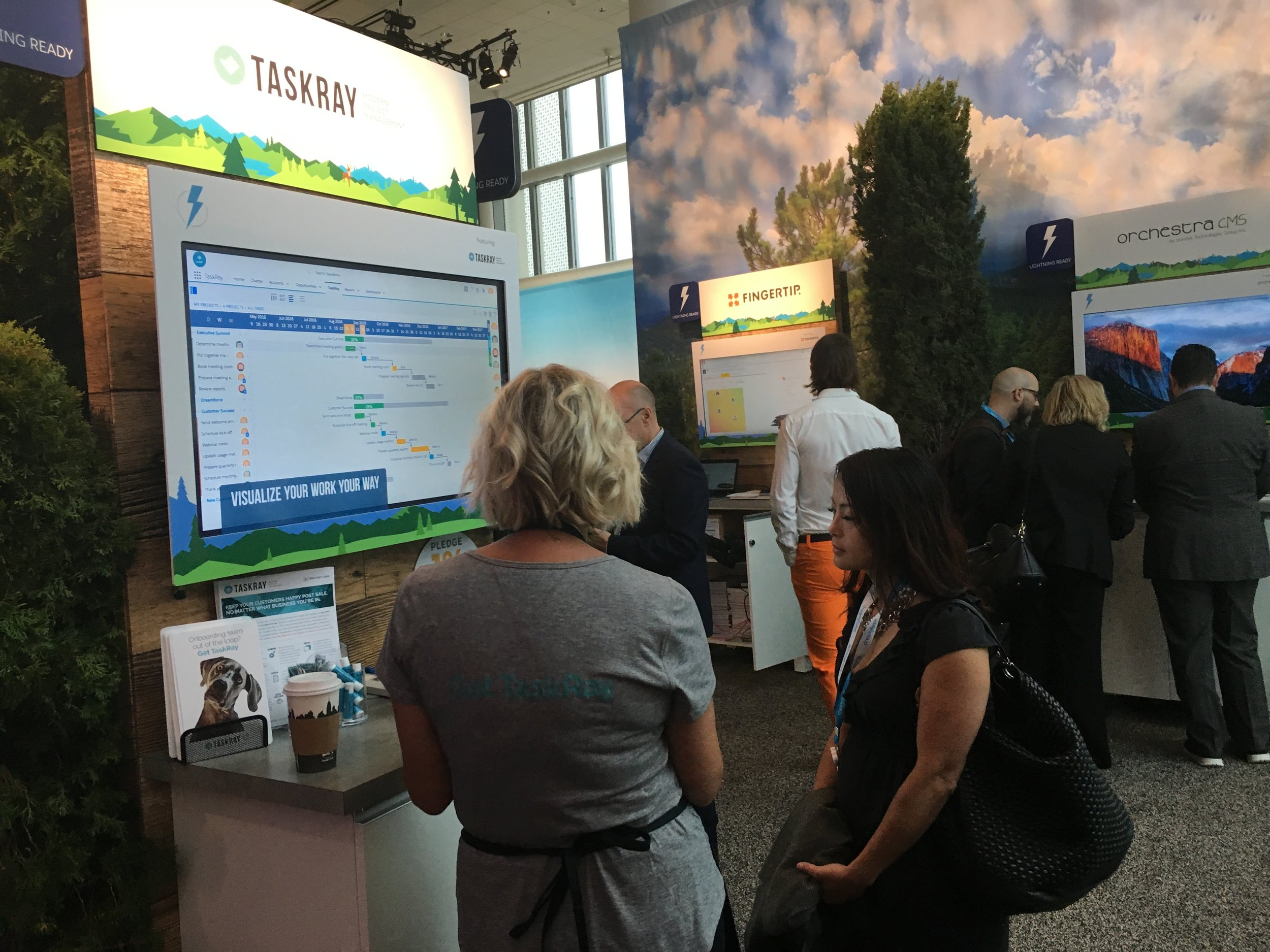 Blakley helping educate a booth visitor about the benefits of TaskRay Lightning Components.