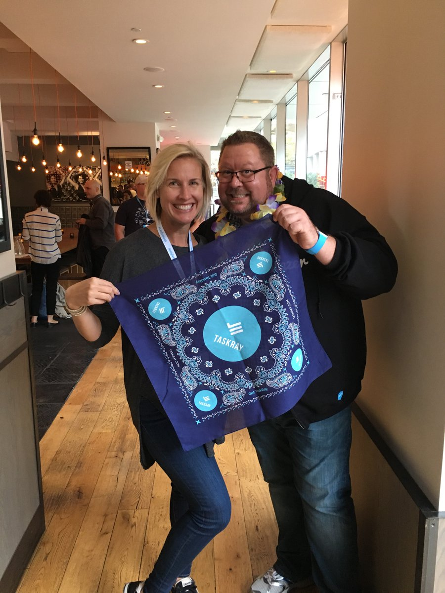 Blakely and Mike Gerholdt holding a TaskRay bandana at the Admin Presenter's Party.
