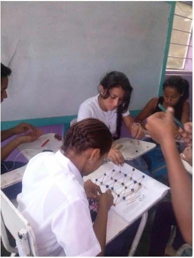 Estudiantes de décimo grado realizando la presentación la estructura cristalinas de los metales en Piedras de Afilar.