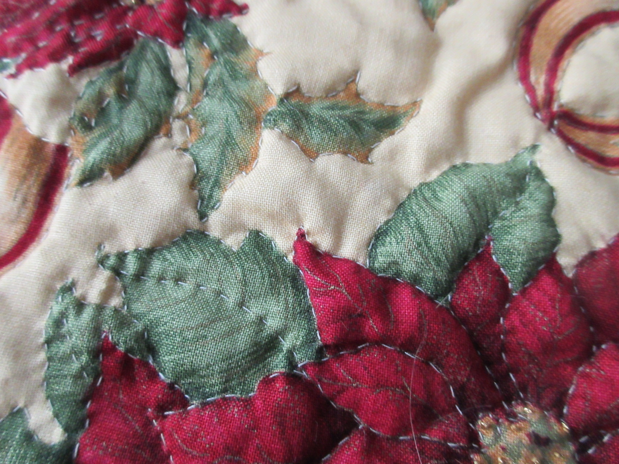 There are gold thread French knots in the centers of each flower (bottom right corner)