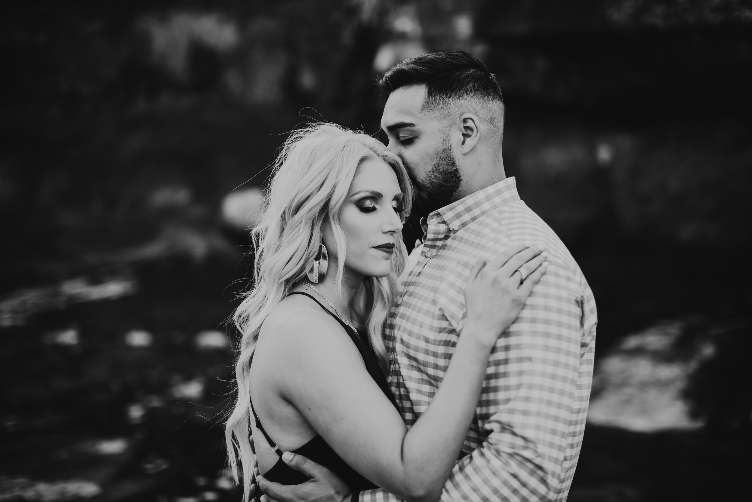 Black and white photo of kiss on the forehead between bride to be and her fiance #engagementphotos #riverfalls #engaged #personality #amarillotexas #engagementphotographer #lifestylephotos #amarillophotographer #locationchoice #texasengagementphotos #engagment #tealawardphotography #wildliferefuge