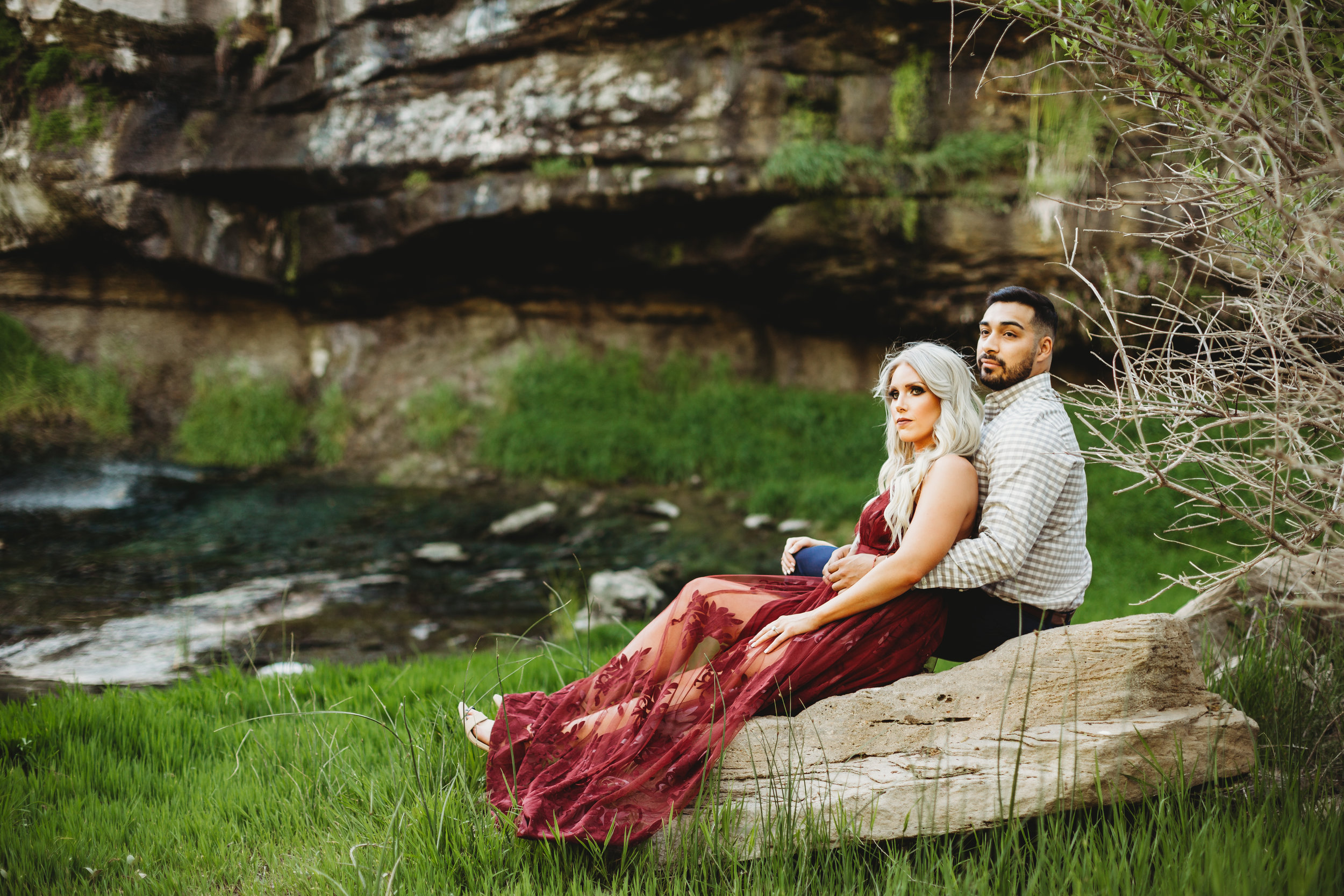 Sitting in the wildlife refuge together with green foliage in the background in ruby red dress #engagementphotos #riverfalls #engaged #personality #amarillotexas #engagementphotographer #lifestylephotos #amarillophotographer #locationchoice #texasengagementphotos #engagment #tealawardphotography #wildliferefuge