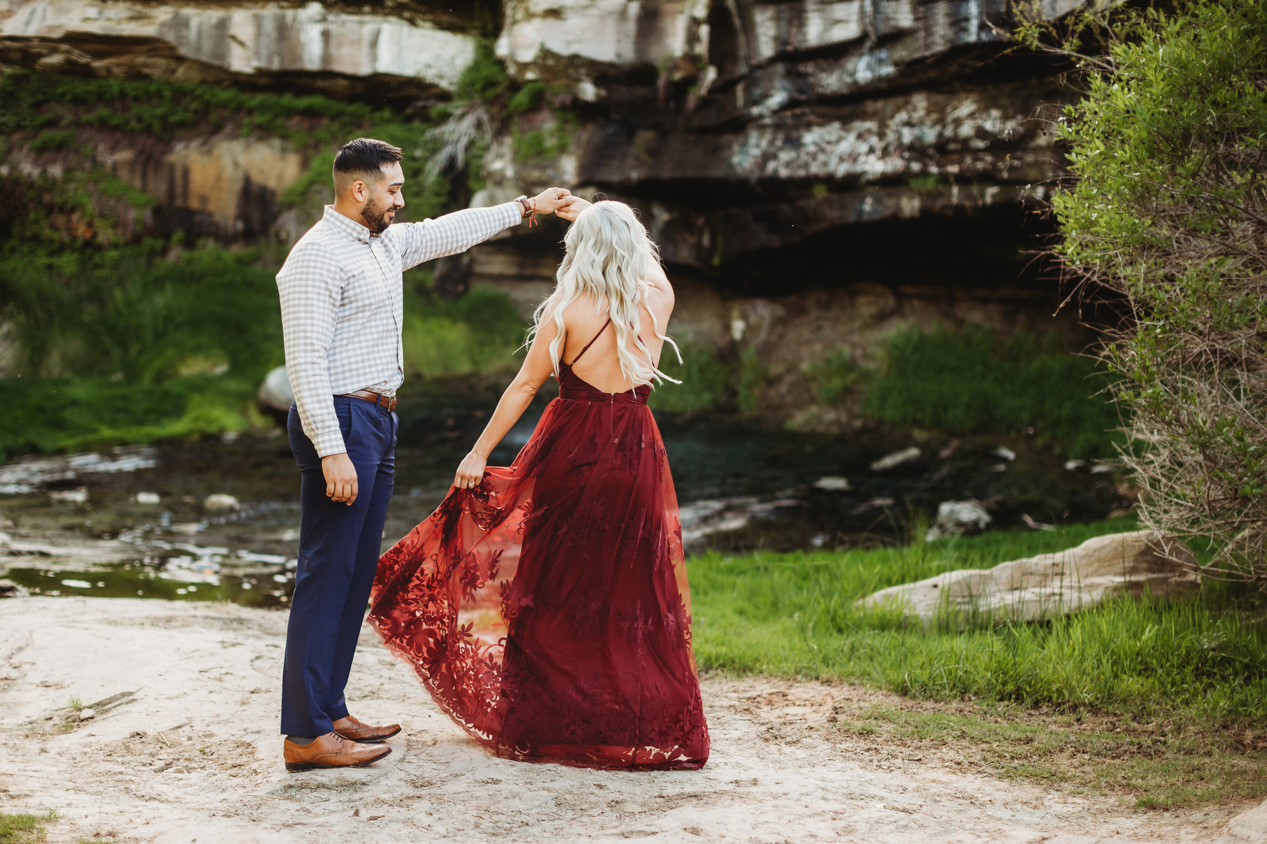 Engaged couple dancing in front of green foliage she is wearing a ruby red formal dress #engagementphotos #riverfalls #engaged #personality #amarillotexas #engagementphotographer #lifestylephotos #amarillophotographer #locationchoice #texasengagementphotos #engagment #tealawardphotography #wildliferefuge