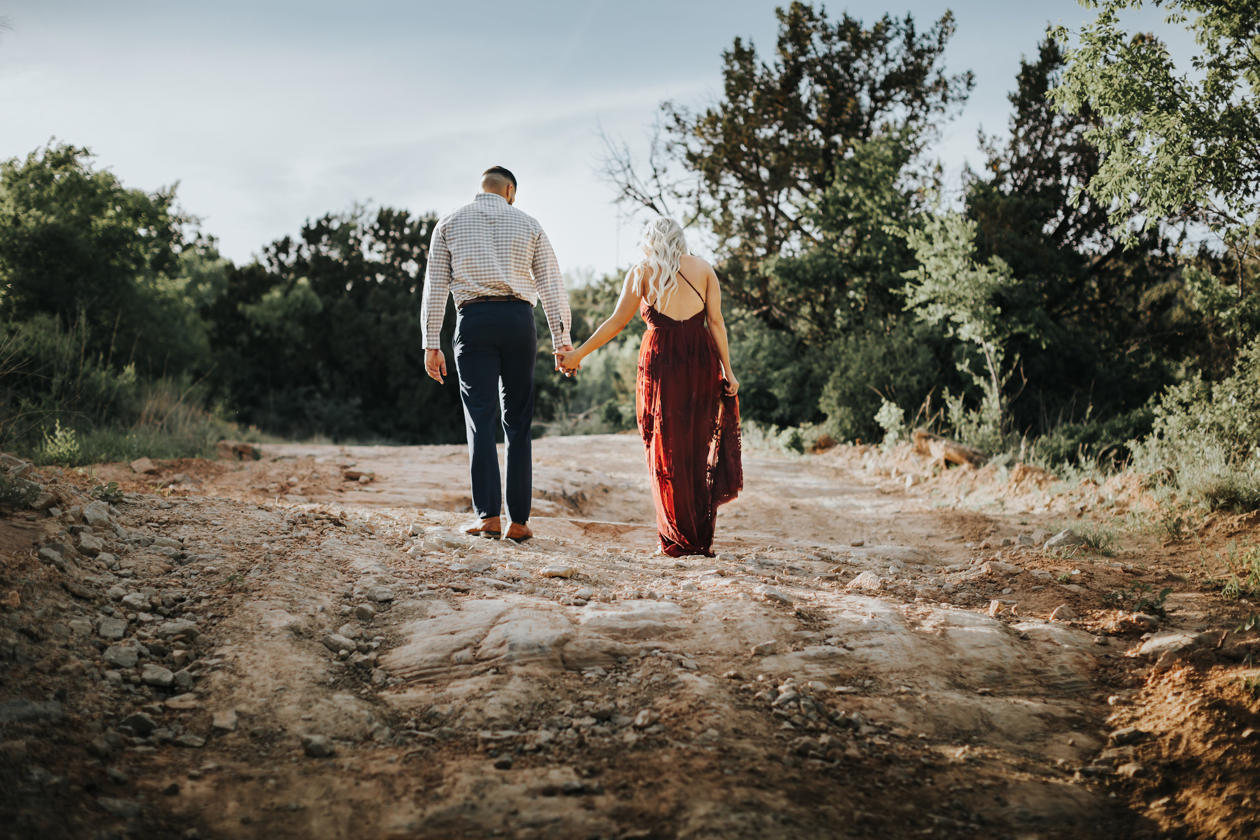 Walking away into the future hand in hand engaged couple walks uphill #engagementphotos #riverfalls #engaged #personality #amarillotexas #engagementphotographer #lifestylephotos #amarillophotographer #locationchoice #texasengagementphotos #engagment #tealawardphotography #wildliferefuge